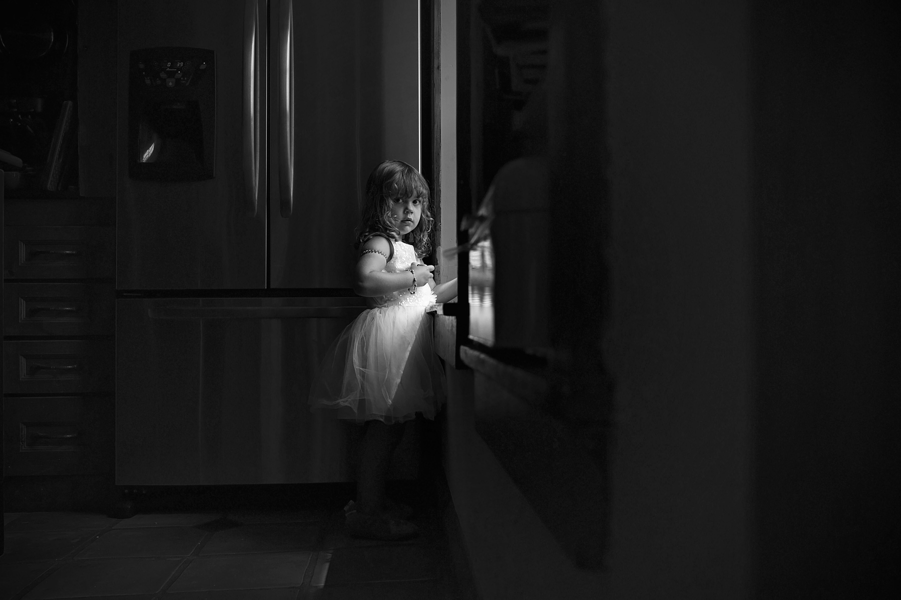 black and white of toddler girl in dress standing by window