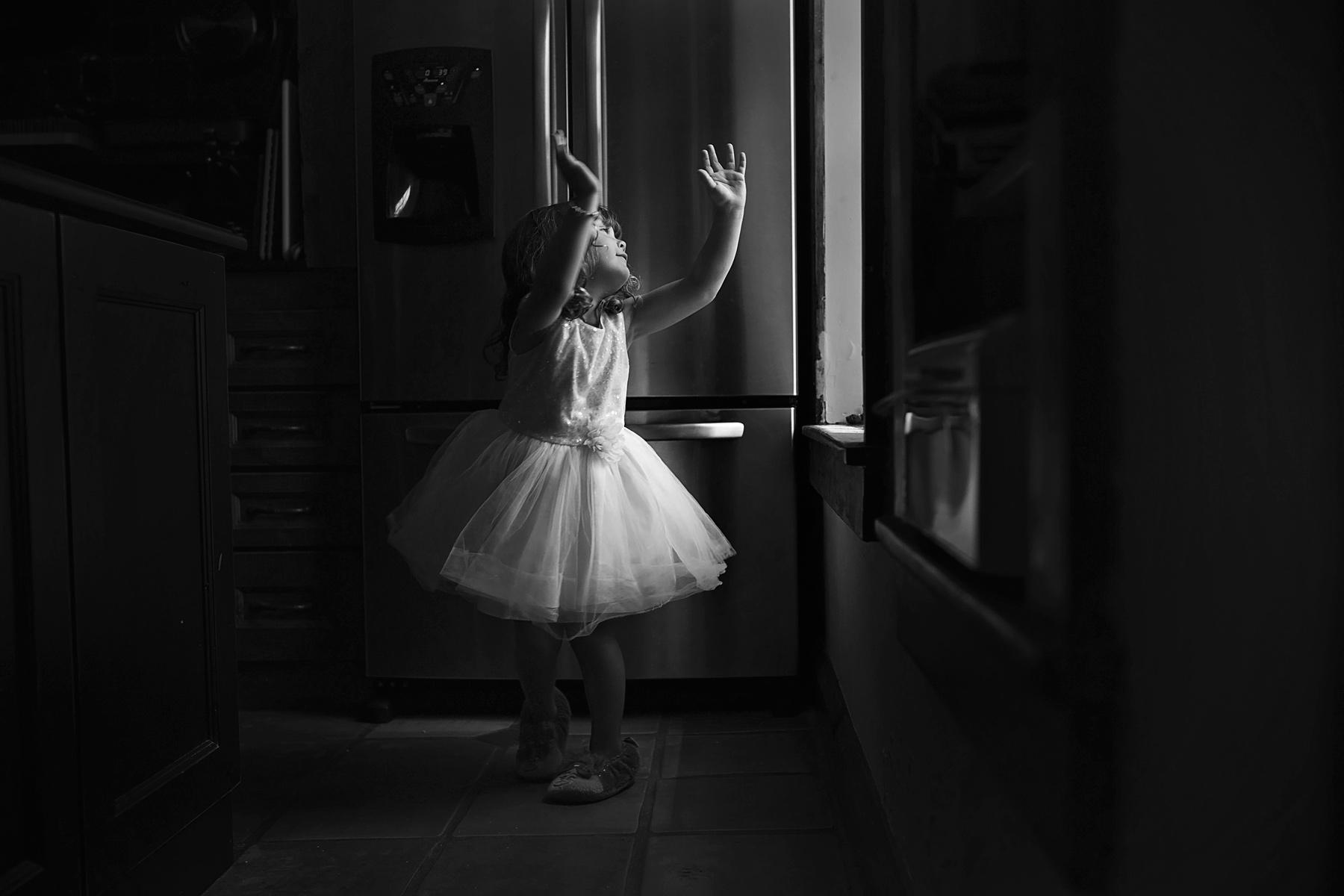little girl dances in ballerina dress in the kitchen