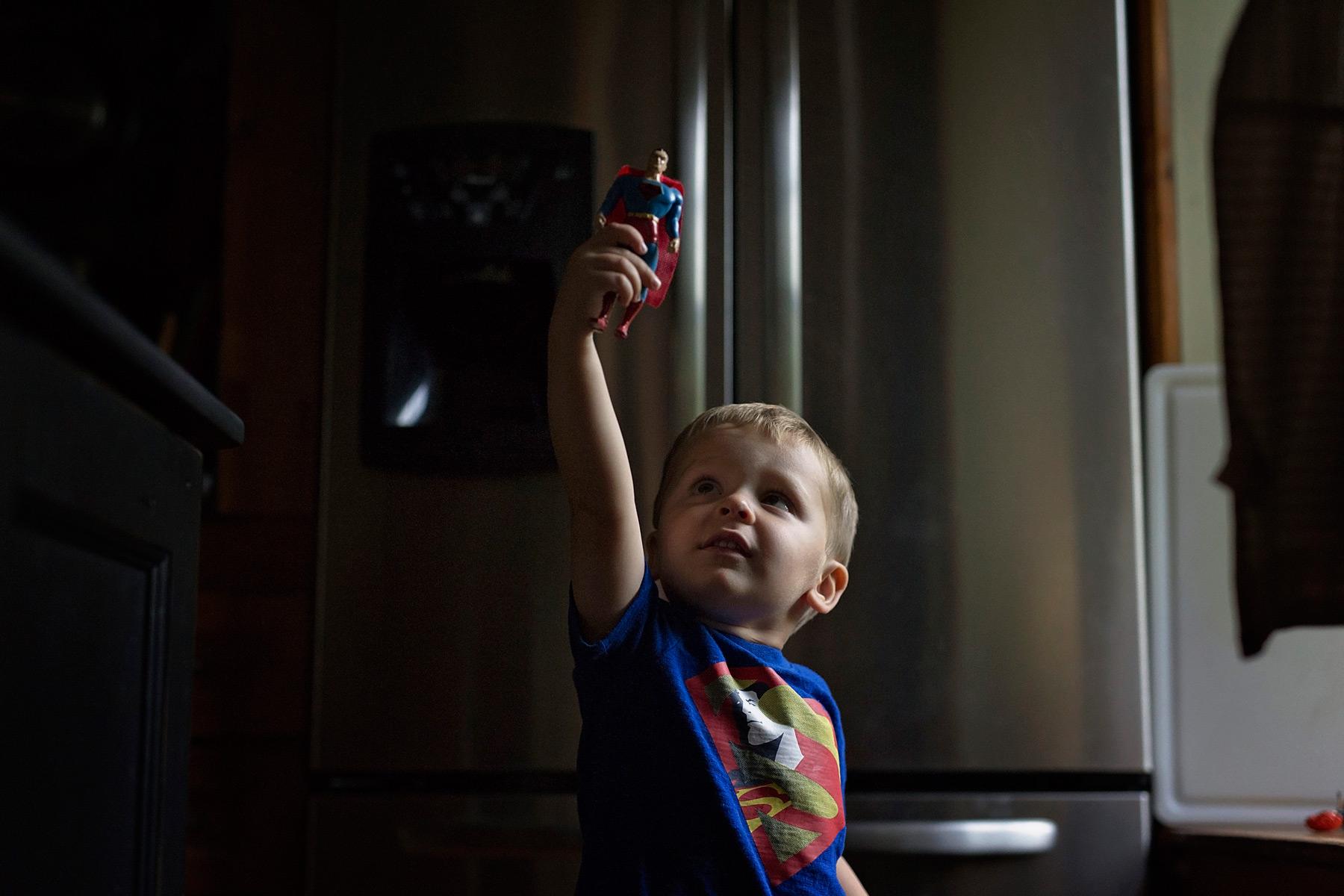 little boy flies superman figure overhead while wearing superman shirt