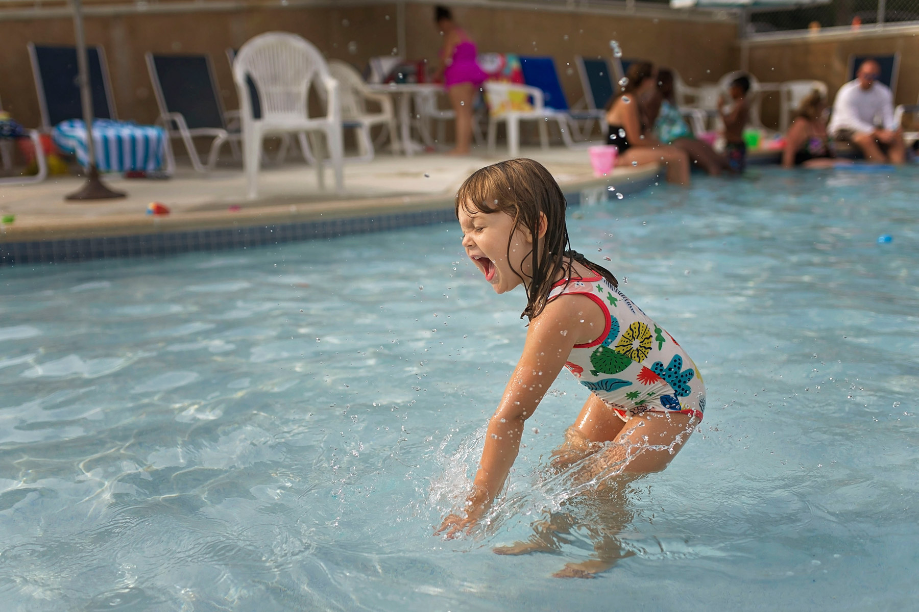 4 year old splashing in the pool