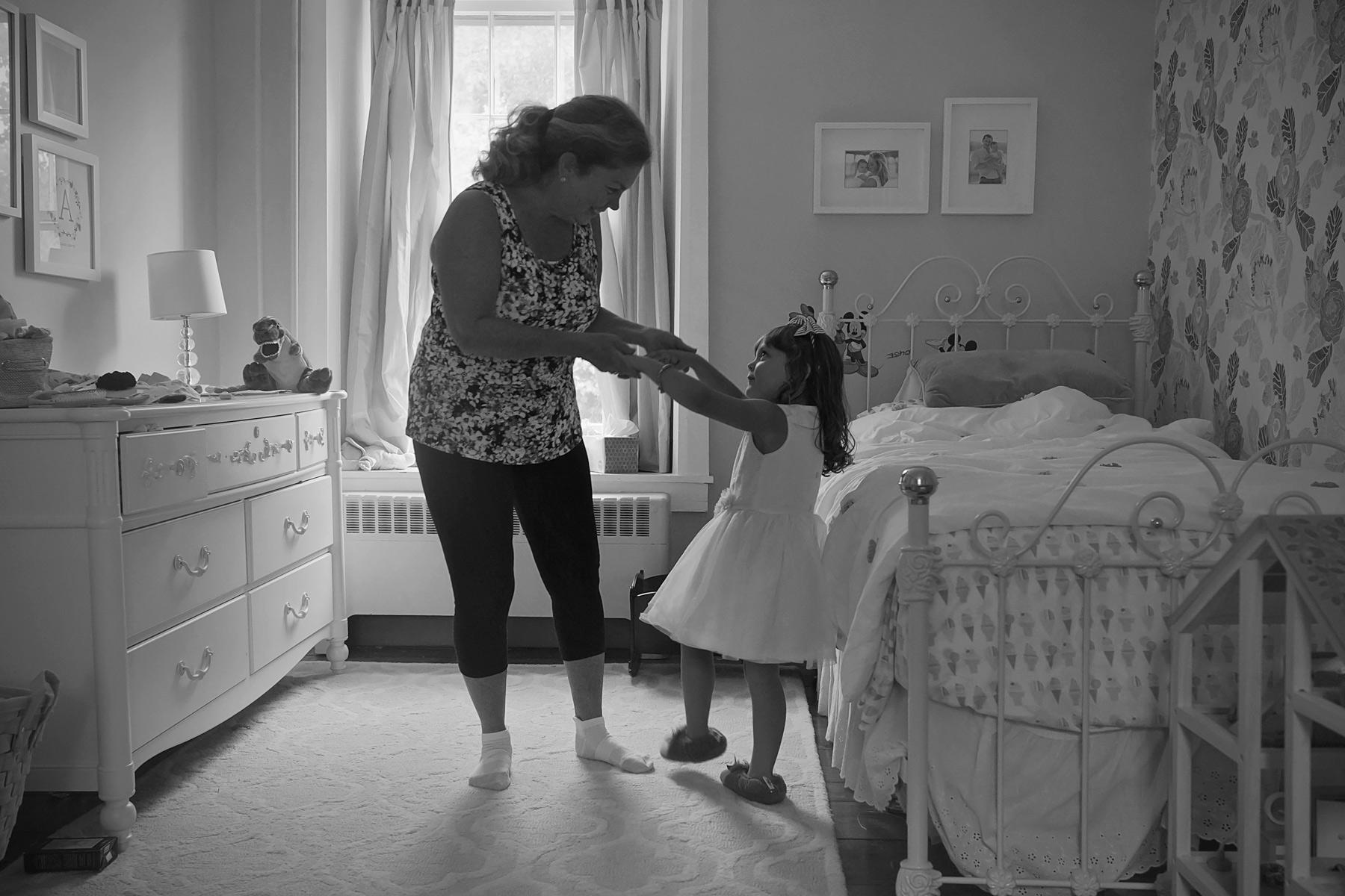 girl dances with grandmother in her bedroom