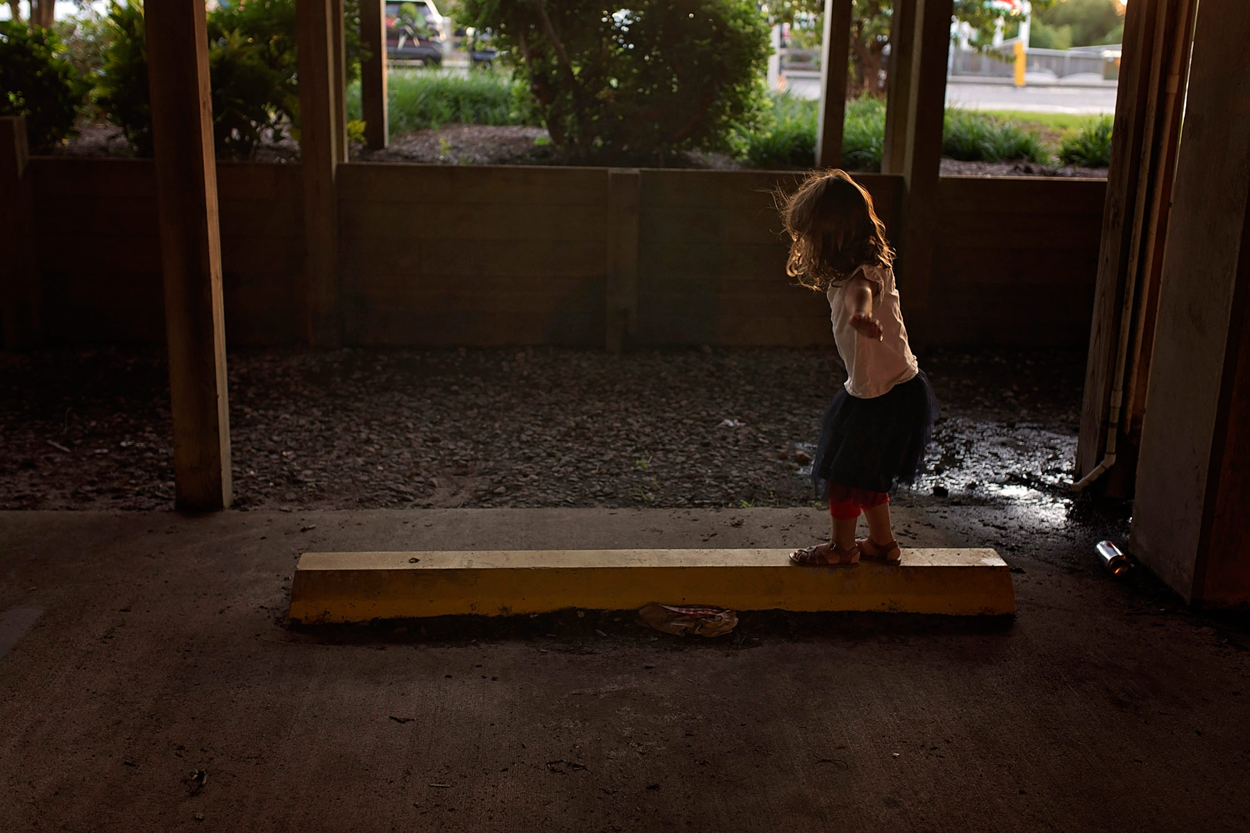 girl balances on parking curb at sundown