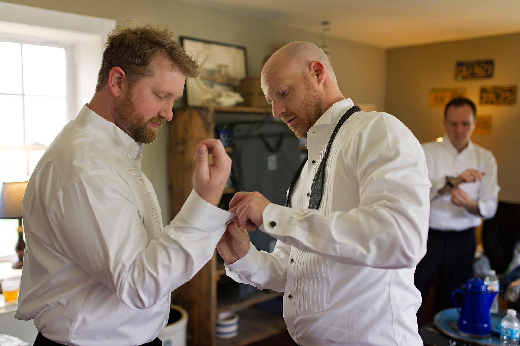 groom helping groomsman wth cuff links