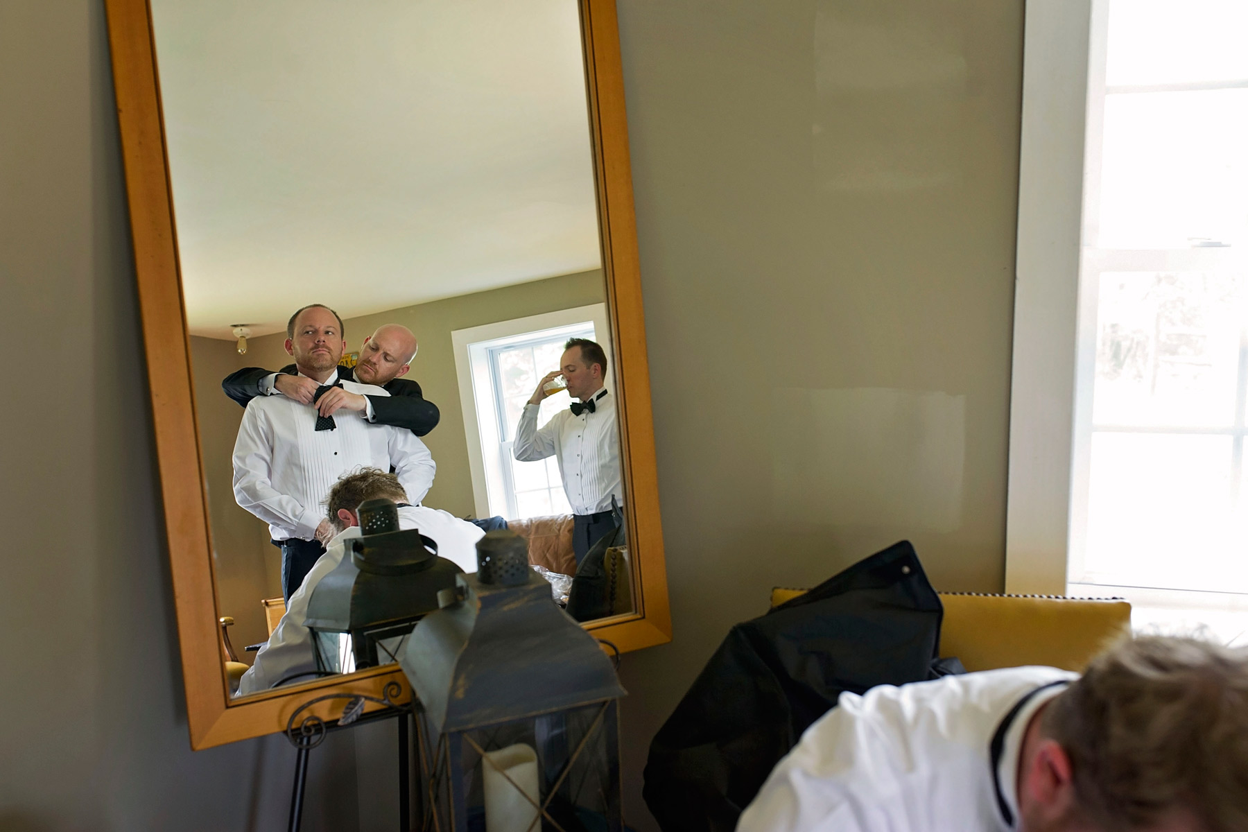 mirror reflection of the groomsmen getting dressed