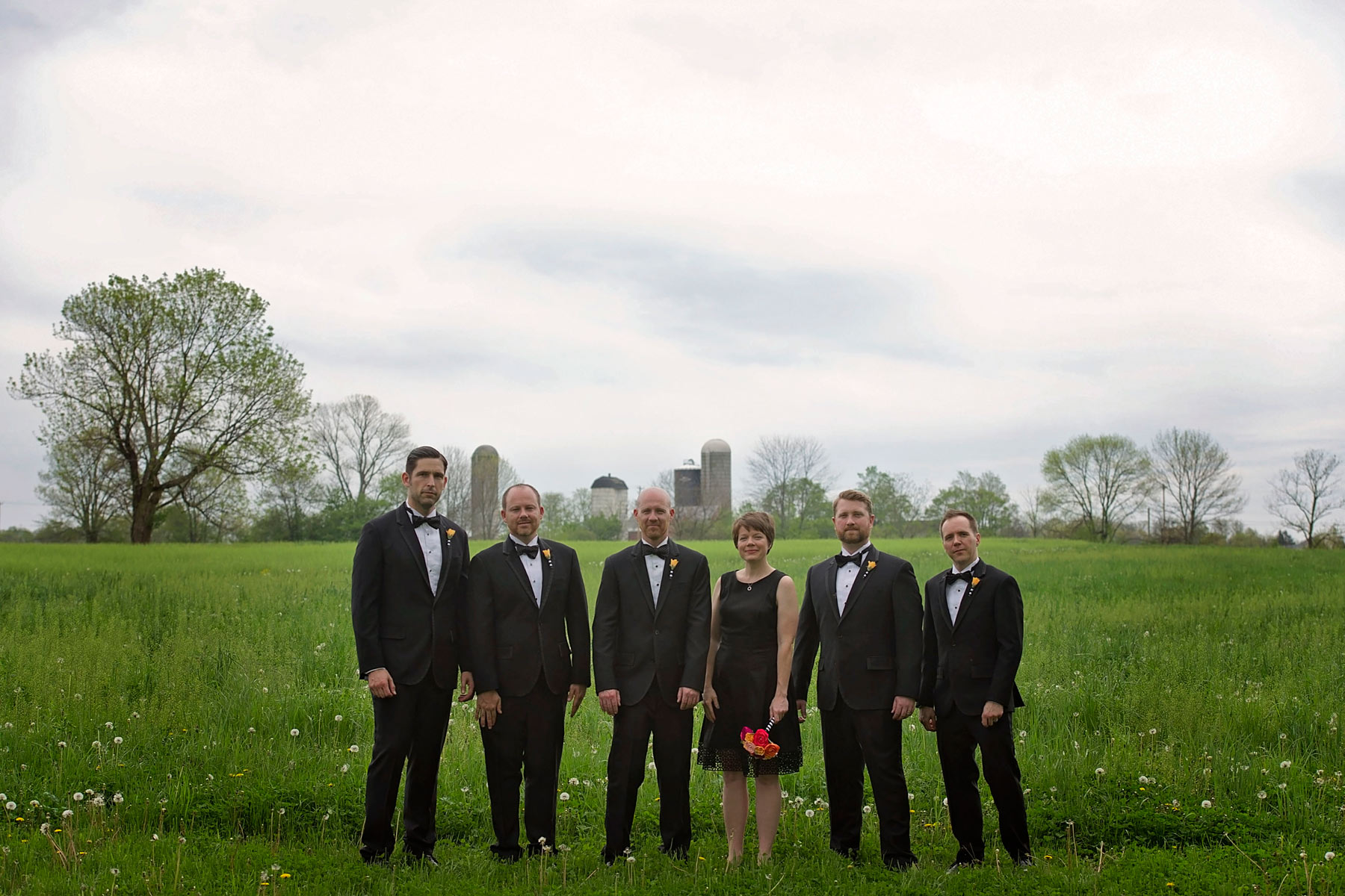 formal shot of groom's wedding party in a field