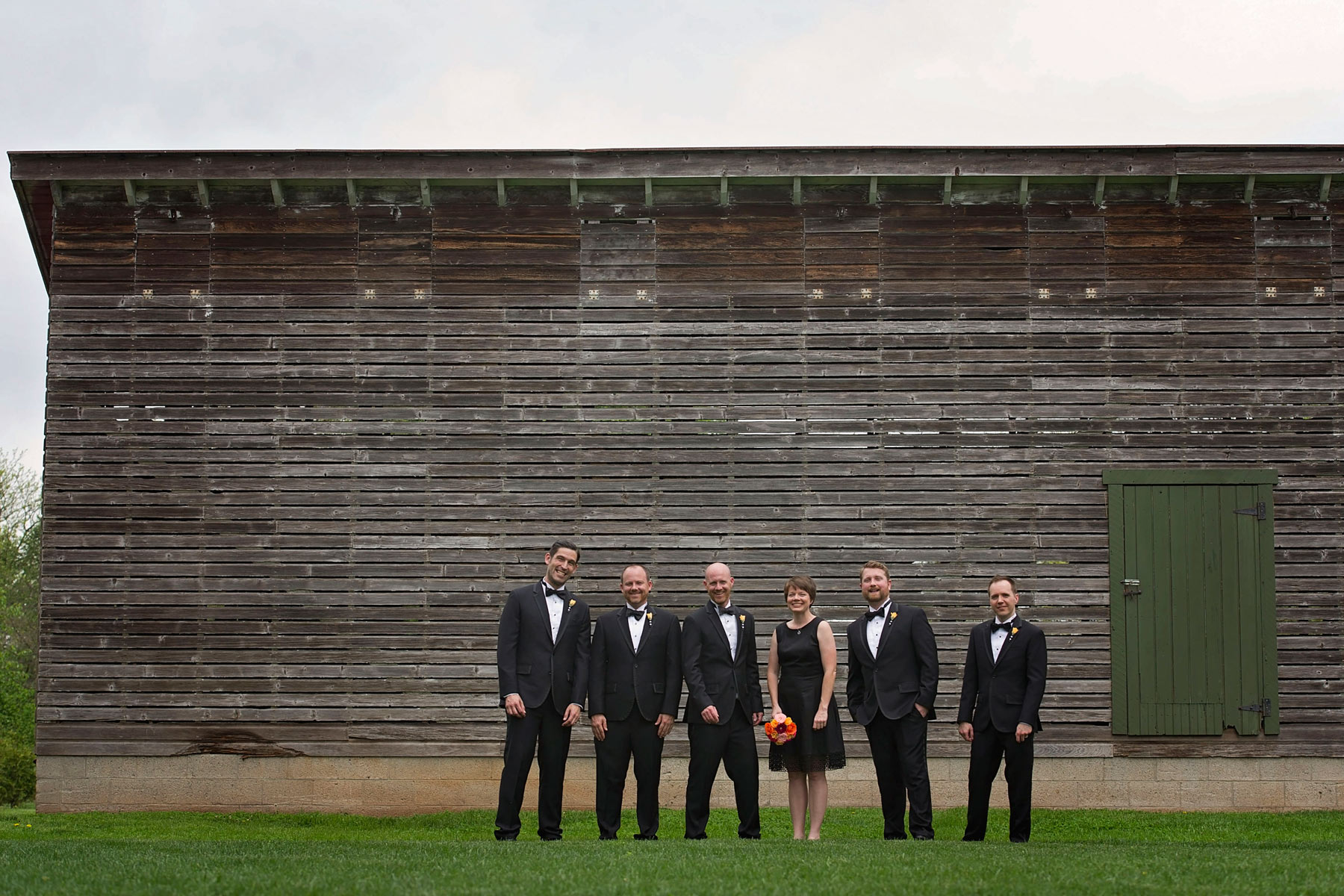 formal shot of groom's wedding party in front of feed barn