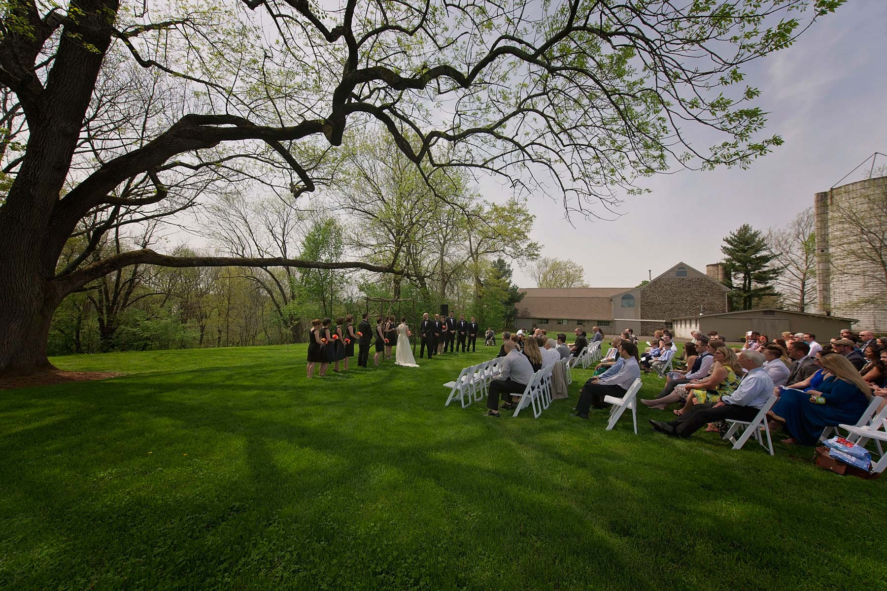 wide angle view of ceremony in field under tree