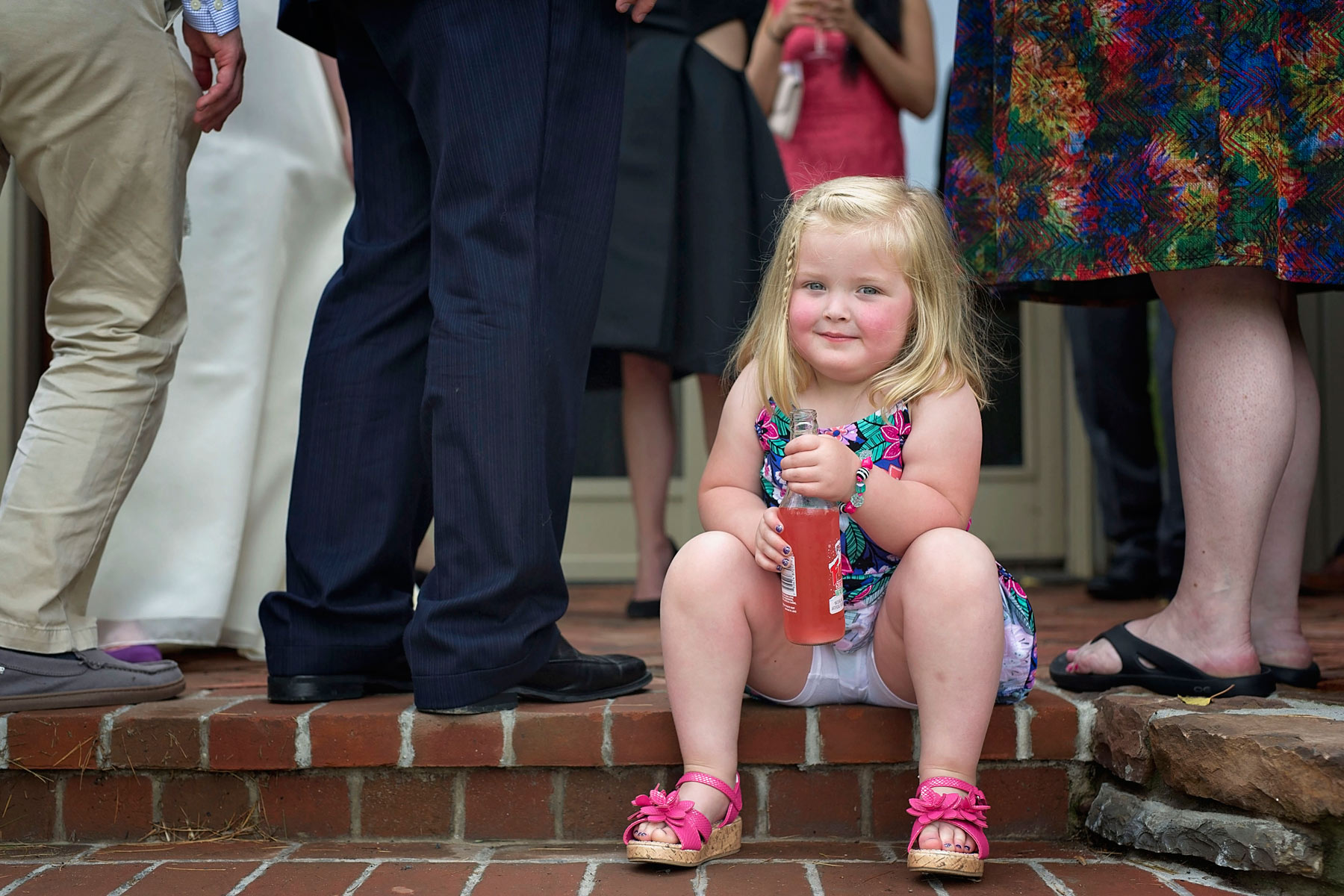 little girl holds a bottle of pink soda while resting on the steps