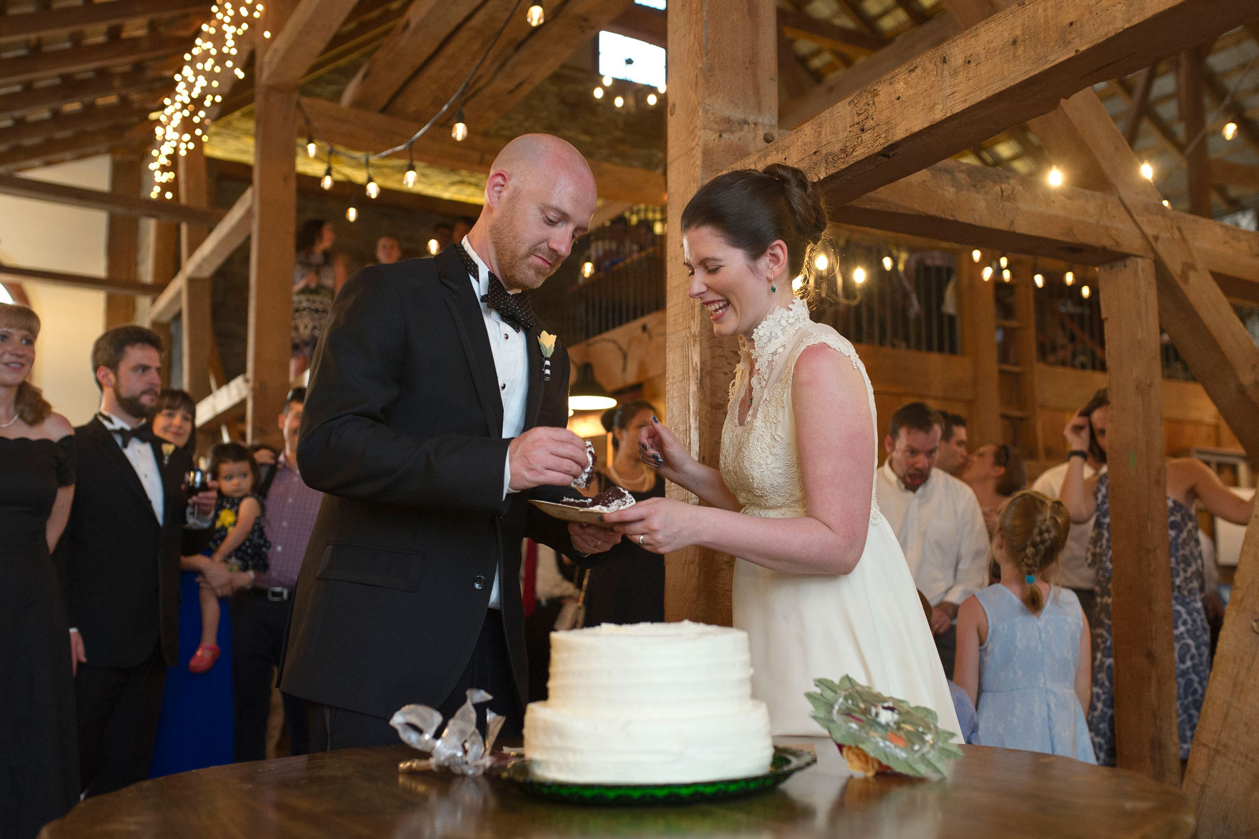 bride and groom cut the cake in the barn at stonebrook