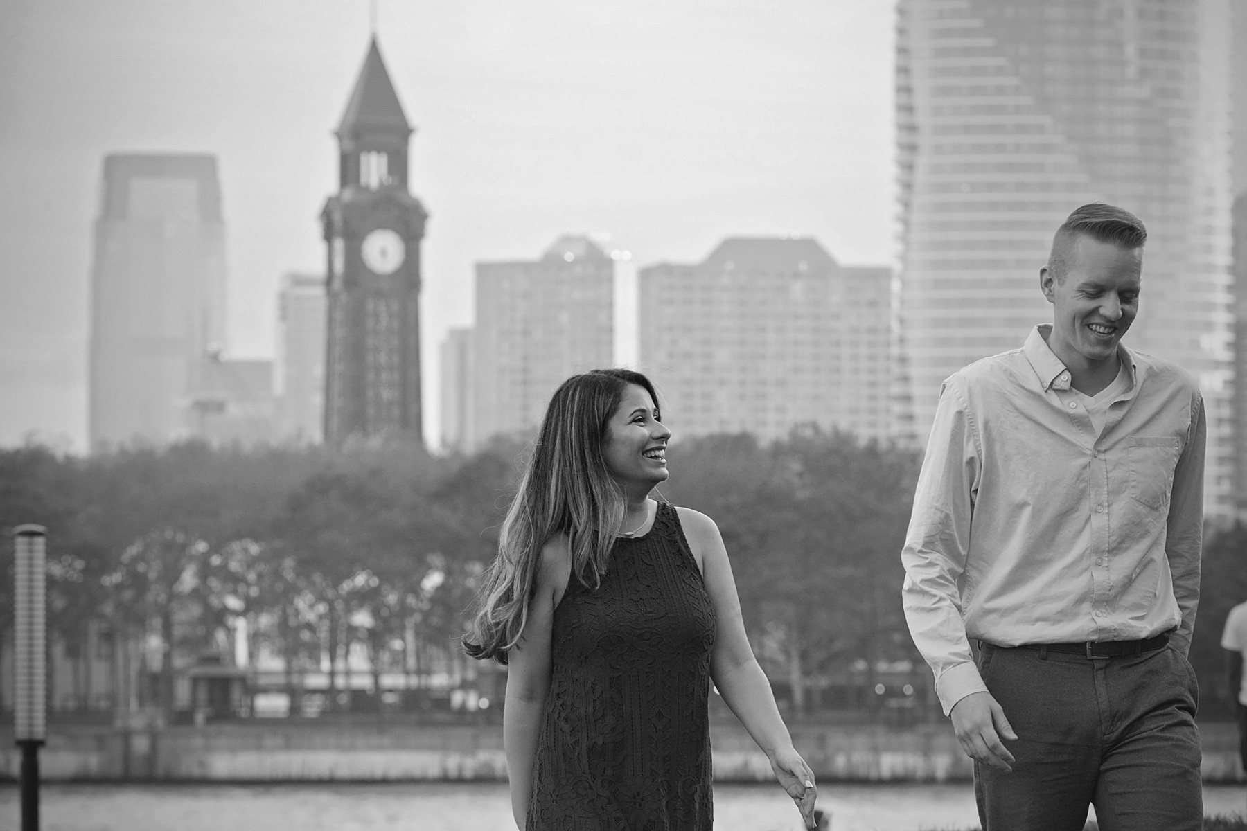 Hoboken_engagement_photographer_black_and_white_of_couple_walking_and_laughing.JPG