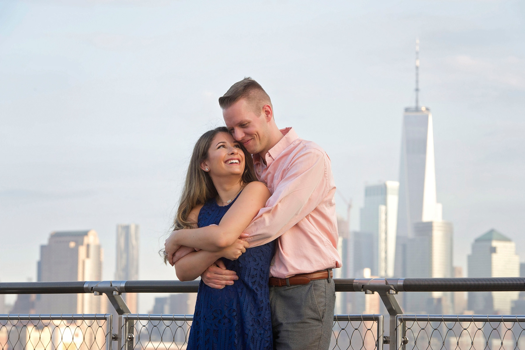 Hoboken_engagement_photographer_couple_pose_in_front_of_the_freedom_tower.JPG