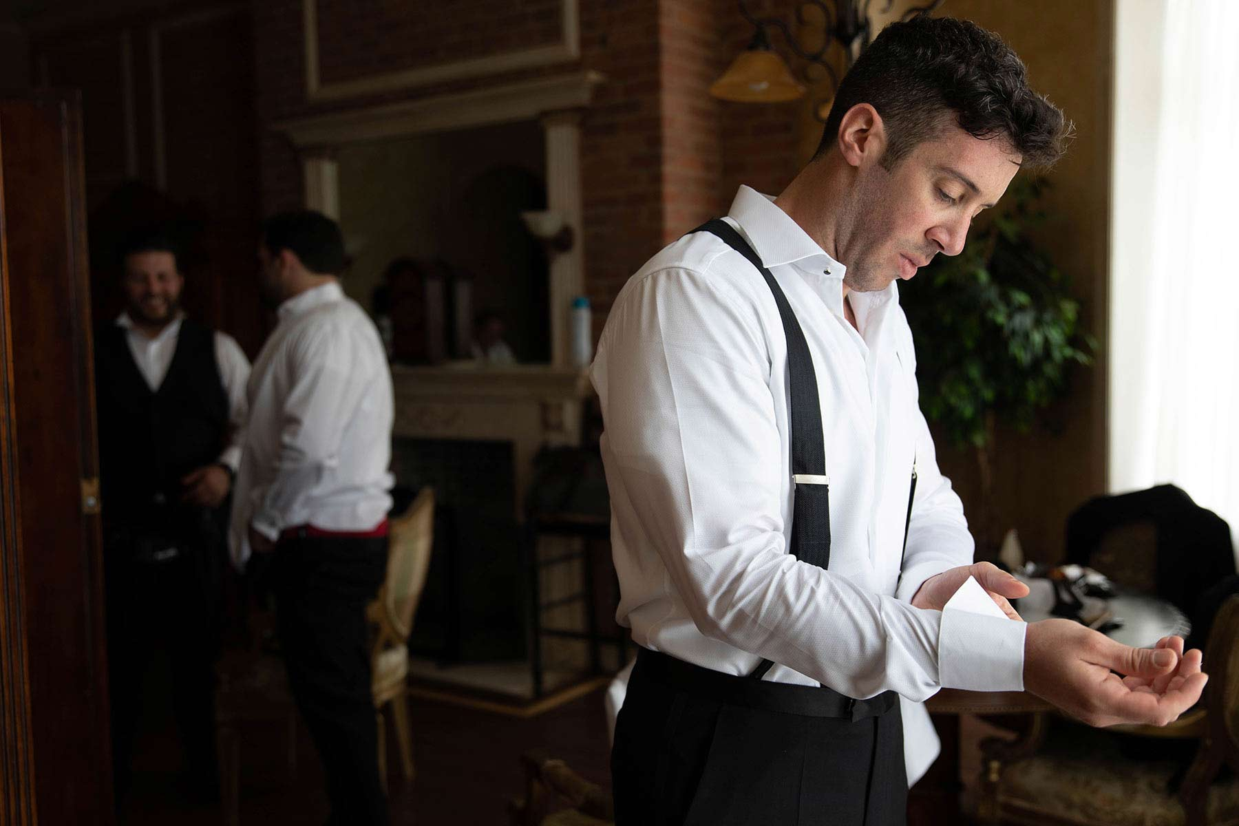 02_groom_adjusts_cuffs_at_Oheka_castle.jpg