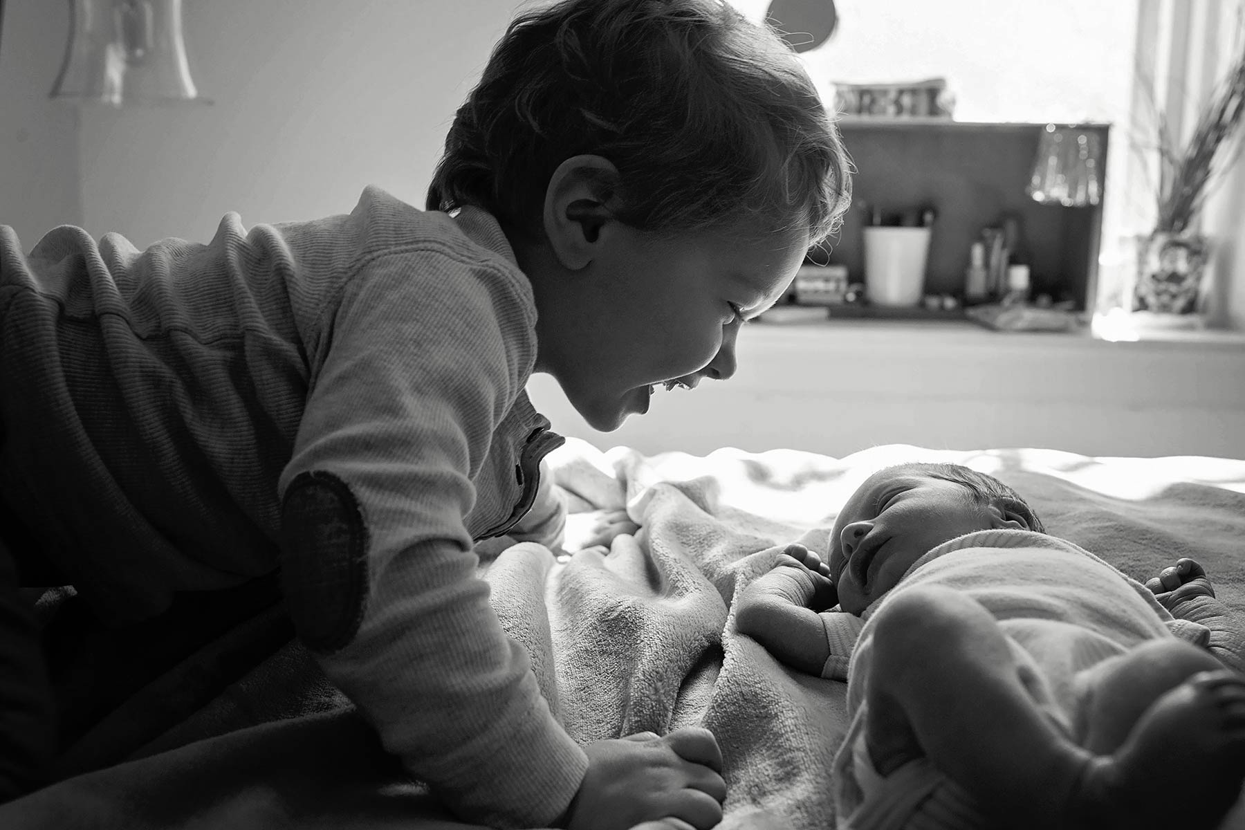toddler smiles at new baby brother