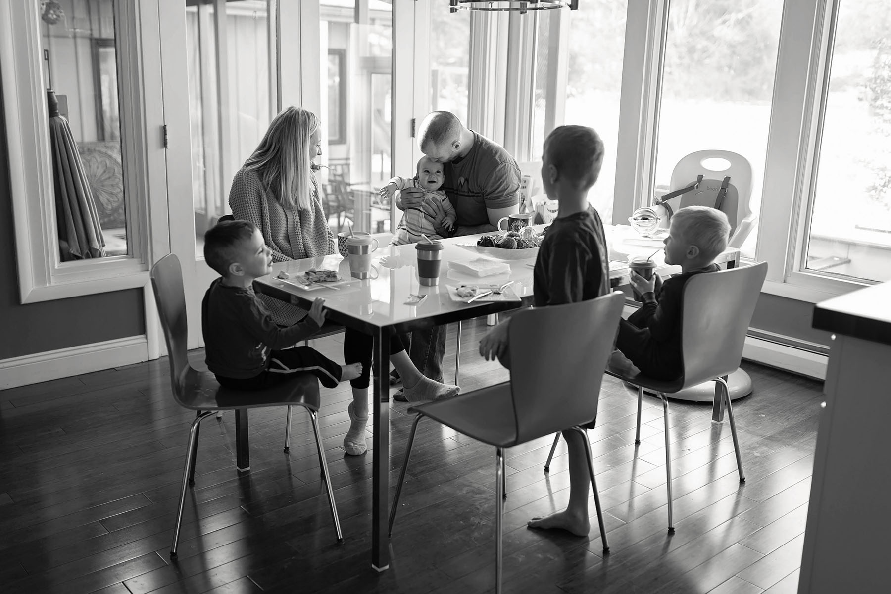 family of six eats breakfast around the kitchen table