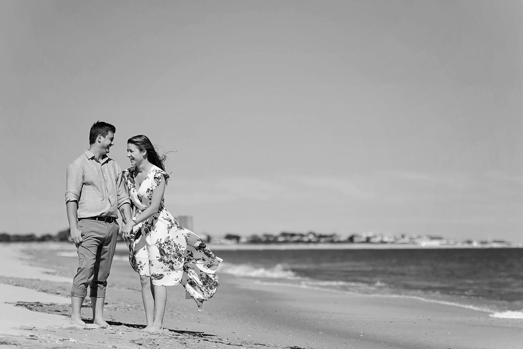 couple holds hands on the beach in cape may nj