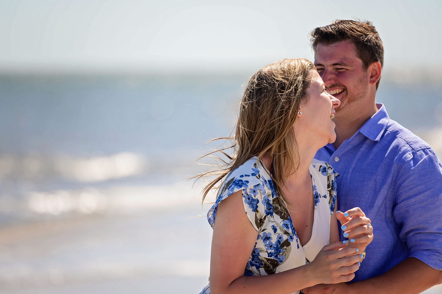 couple laughs together on the beach