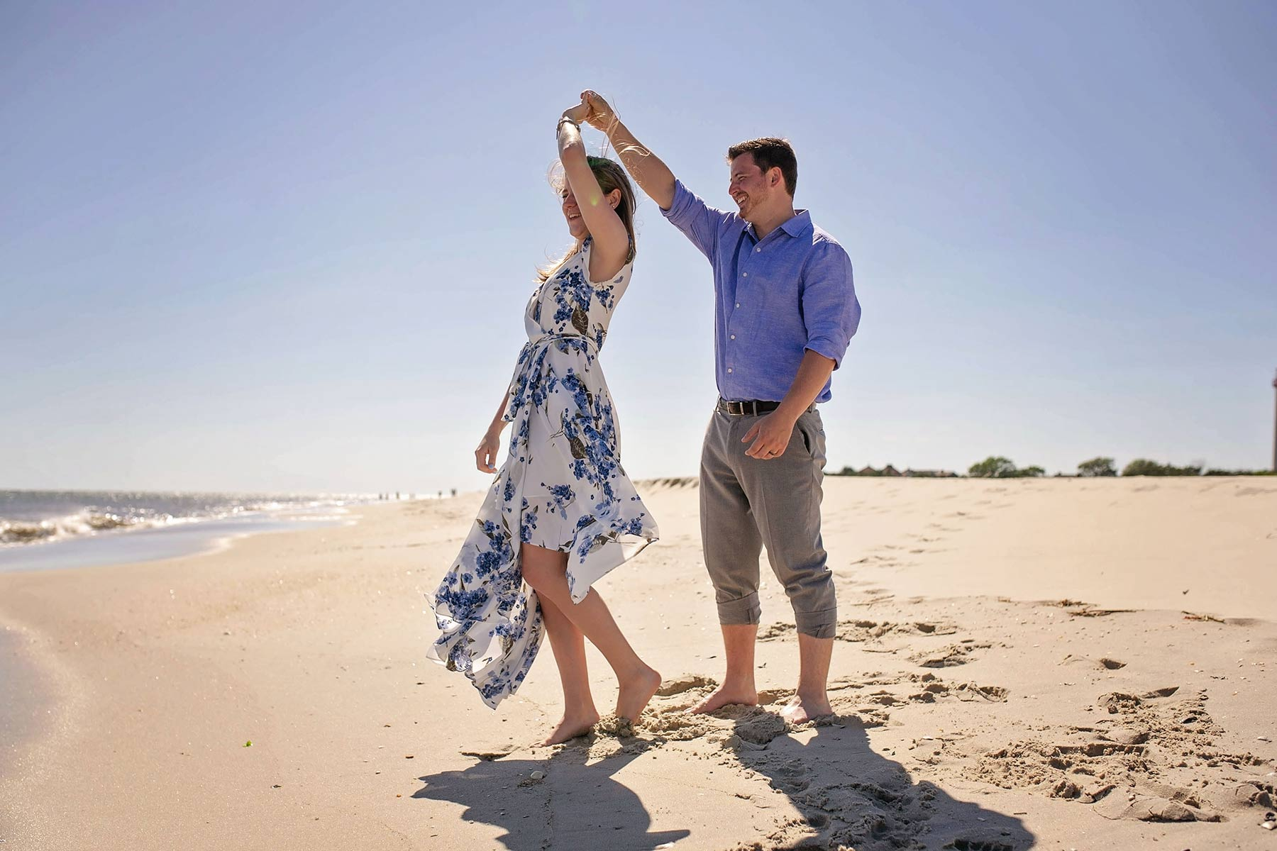 man dances with and twirls woman on the beach