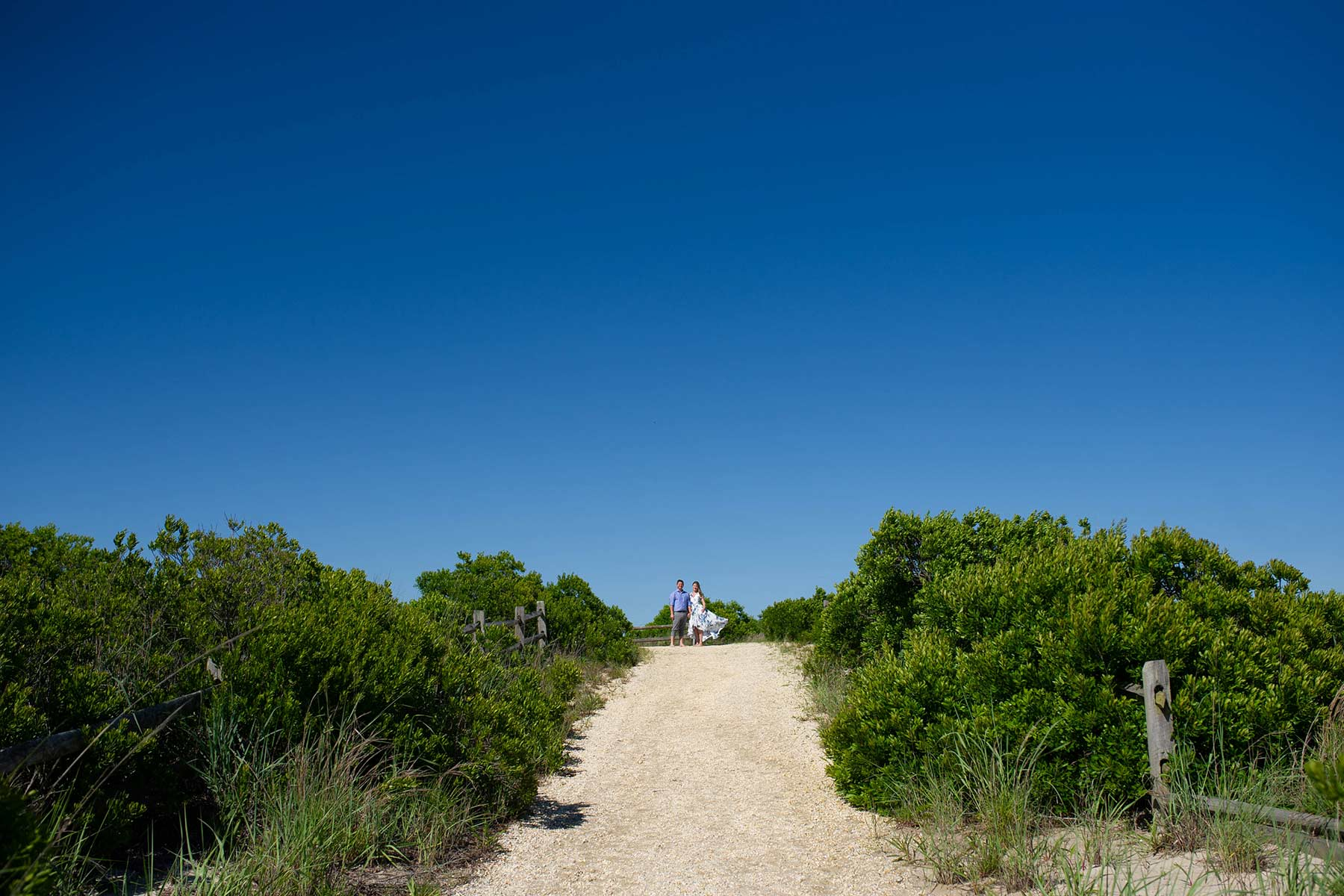 couple stands at the top of beach path in cape may nj