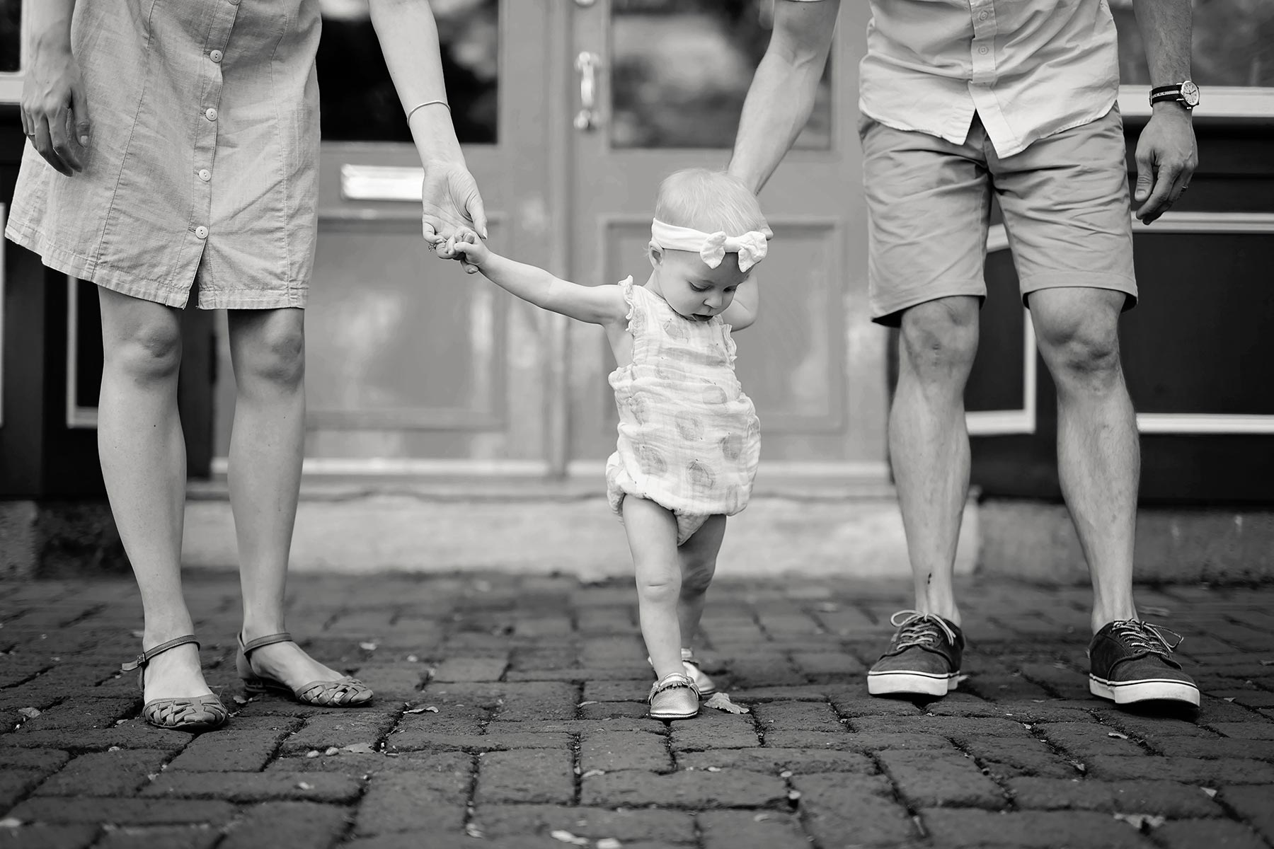 baby walks on cobblestone holding mom and dad's hands