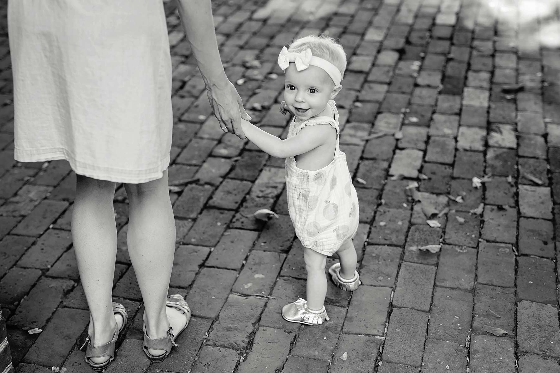 one year old baby girl walks holding mom's hand