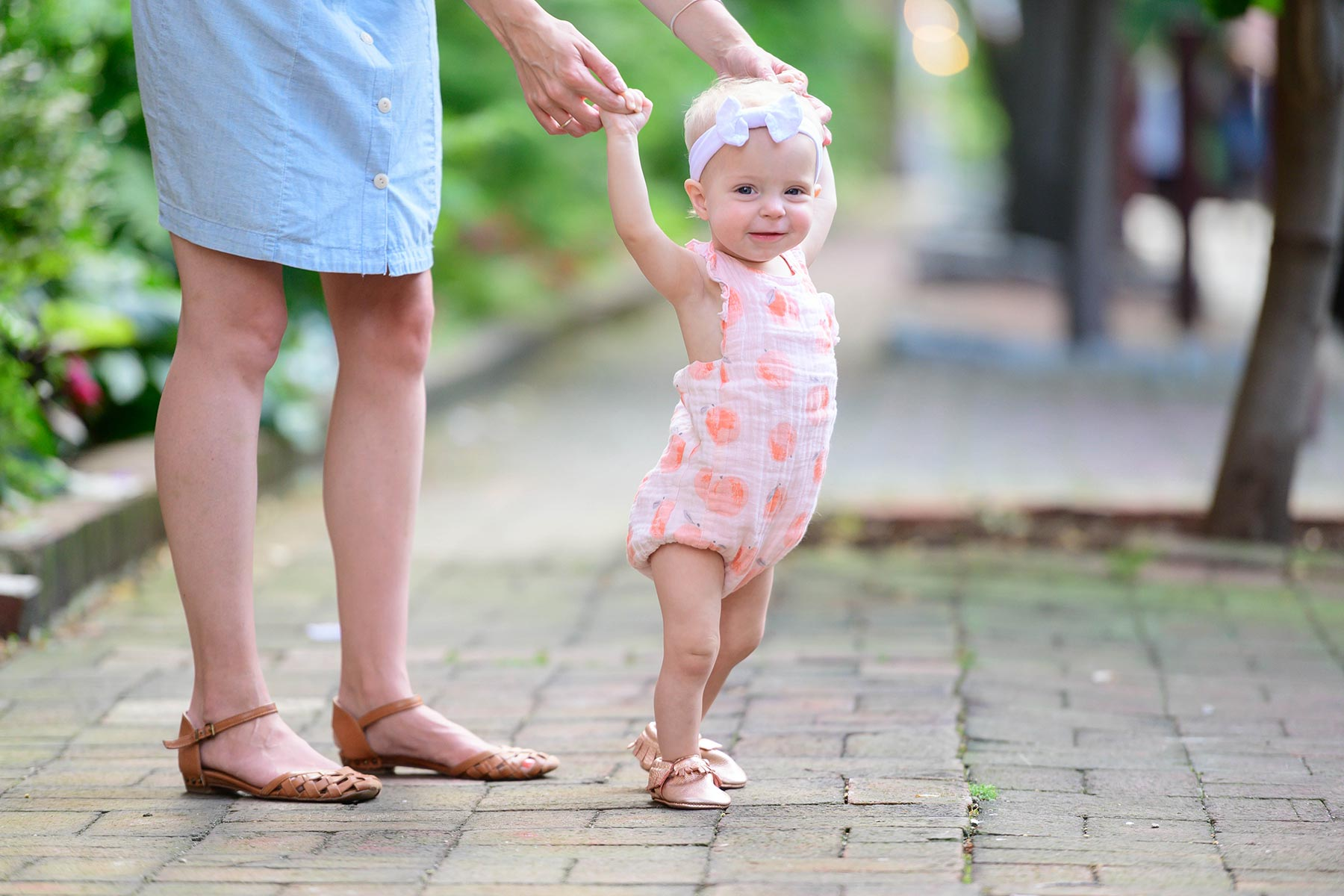 baby girl takes first steps looking very proud