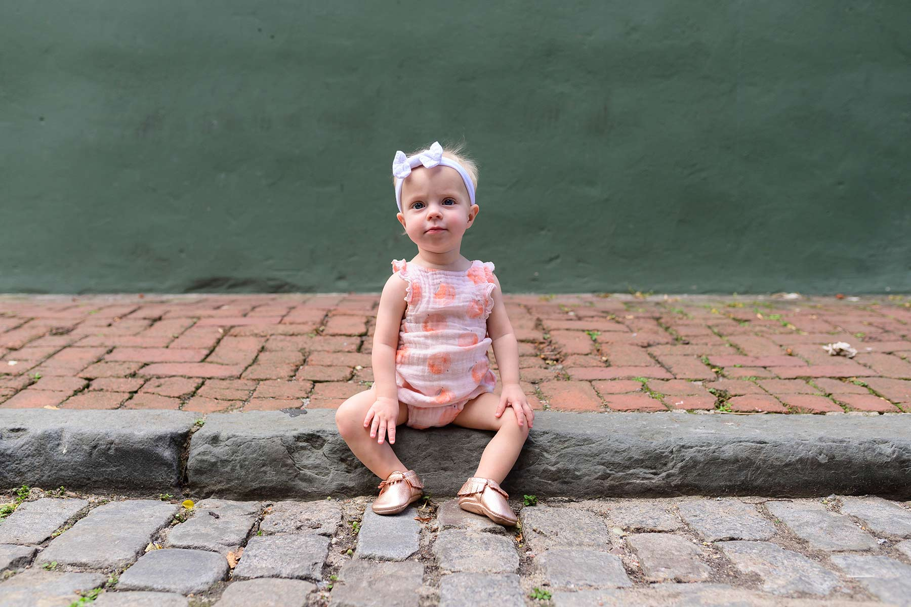 baby girl sits stoically on the street in Philadelphia