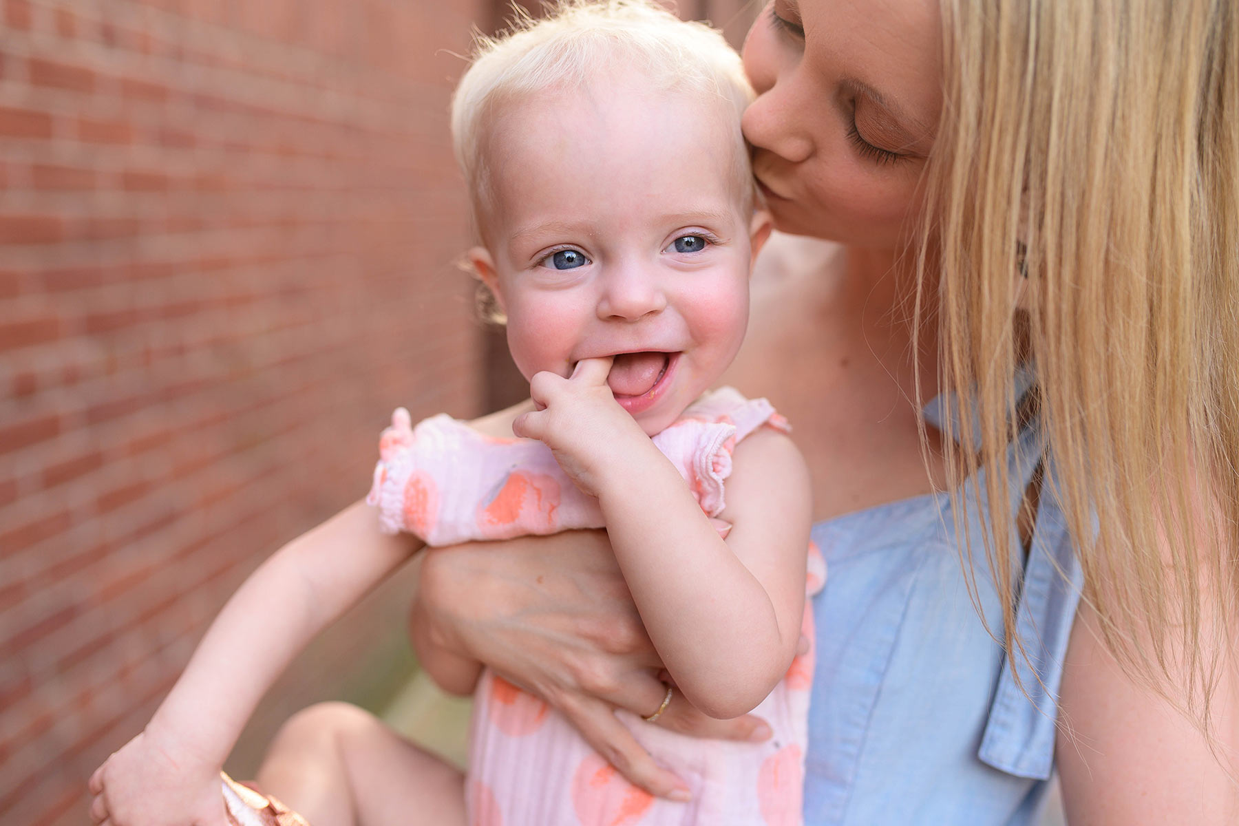 baby girl looks happy as mom kisses her head