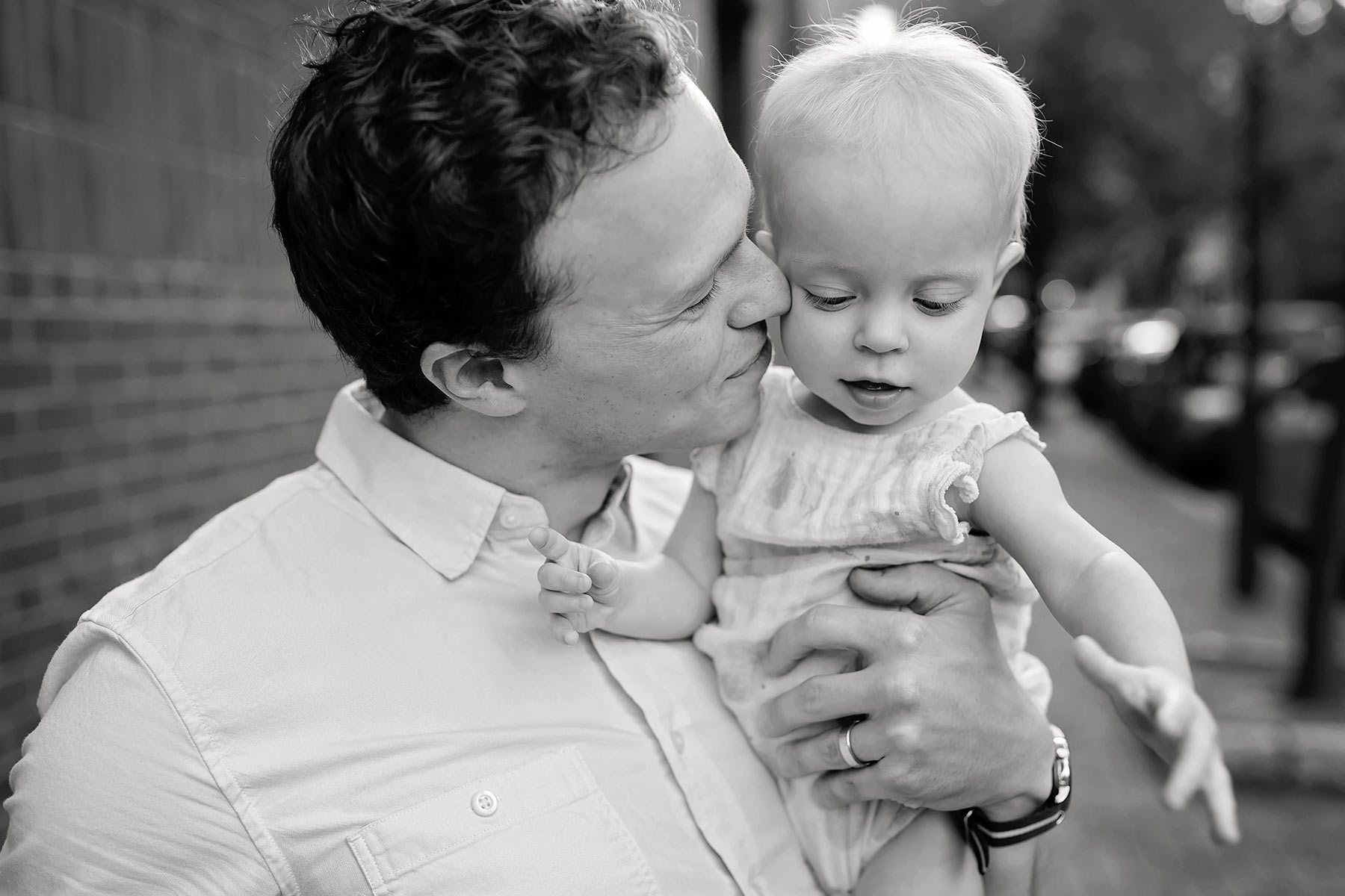 dad nuzzles one year old baby girl