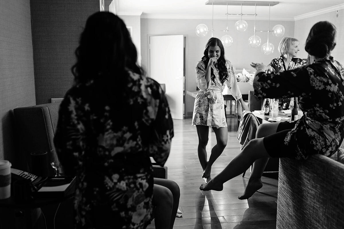 A bride laughs at her bridesmaid while getting ready.