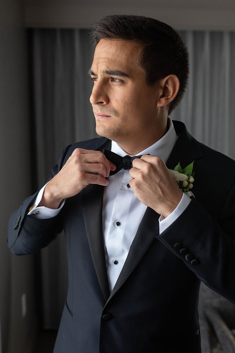 A groom straightens his bowtie.