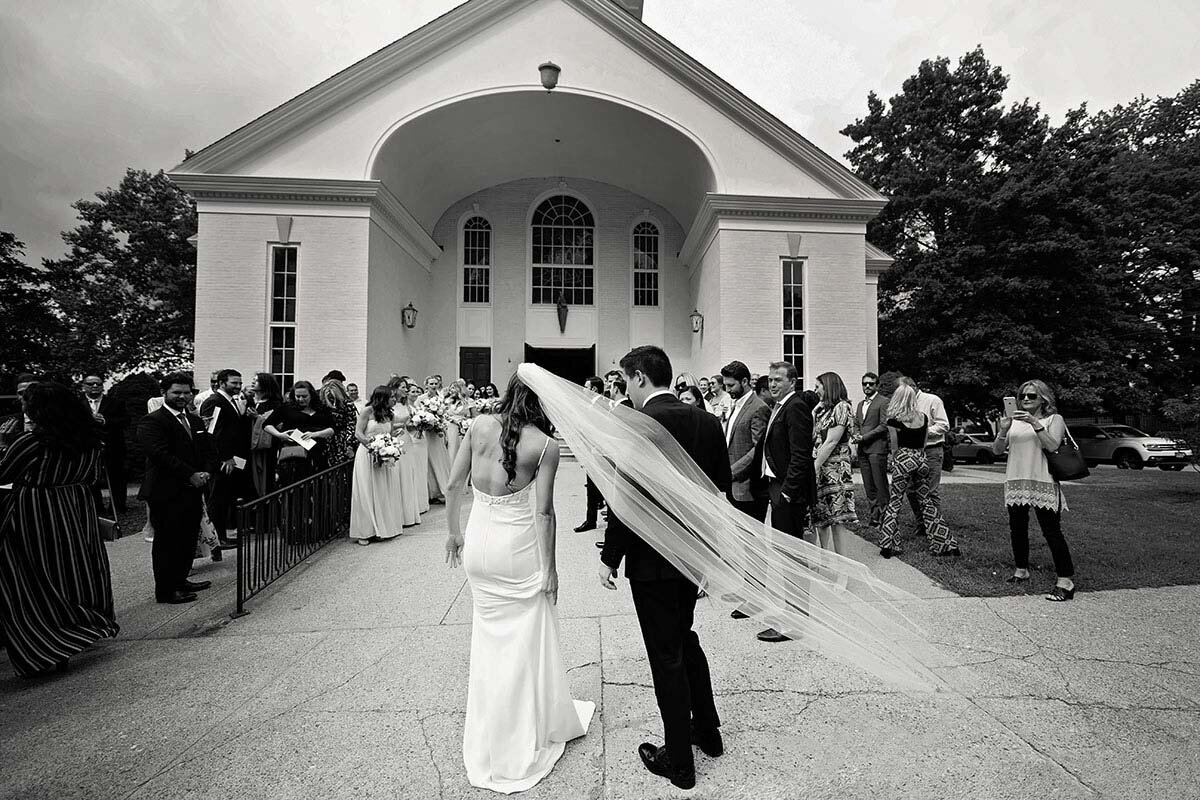A bride's veil blows in the wind outside the church.