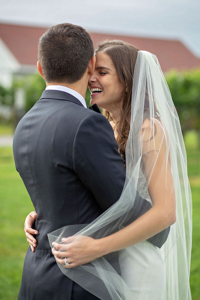 Bride laughs with groom at Jonathan Edwards Winery.