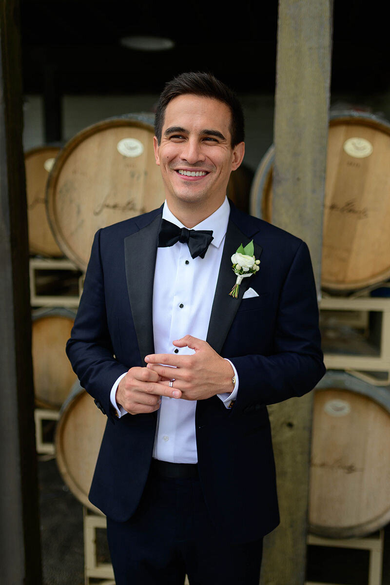 Groom stands in front of wine barrels on his wedding day.