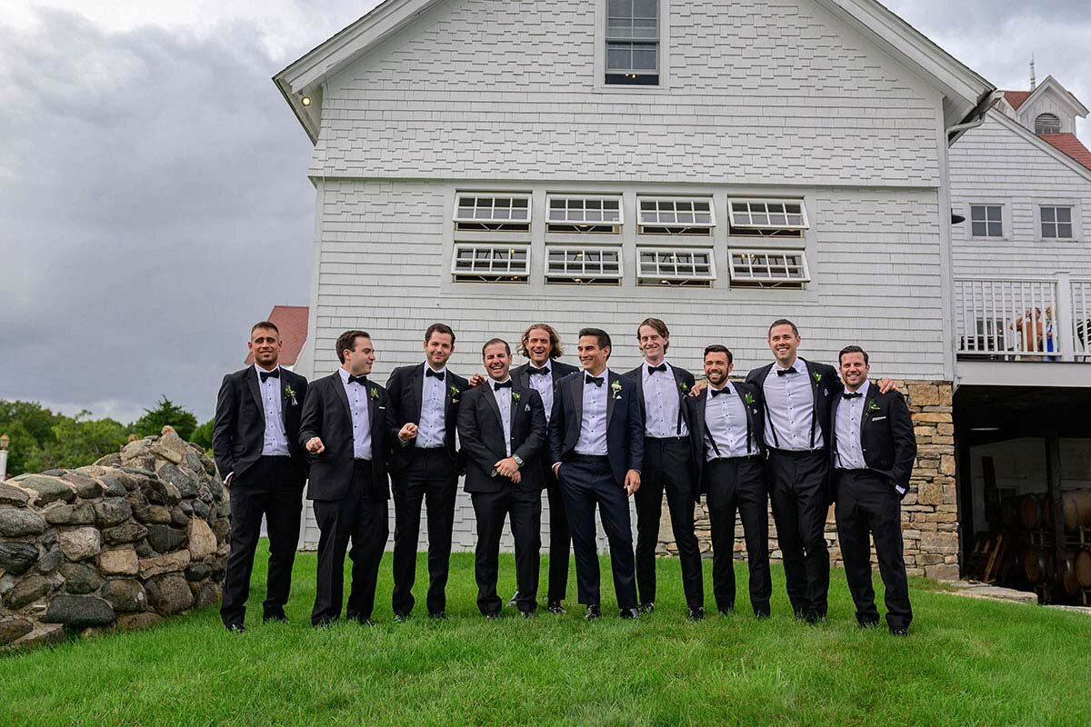 Groomsmen stand together and laugh.