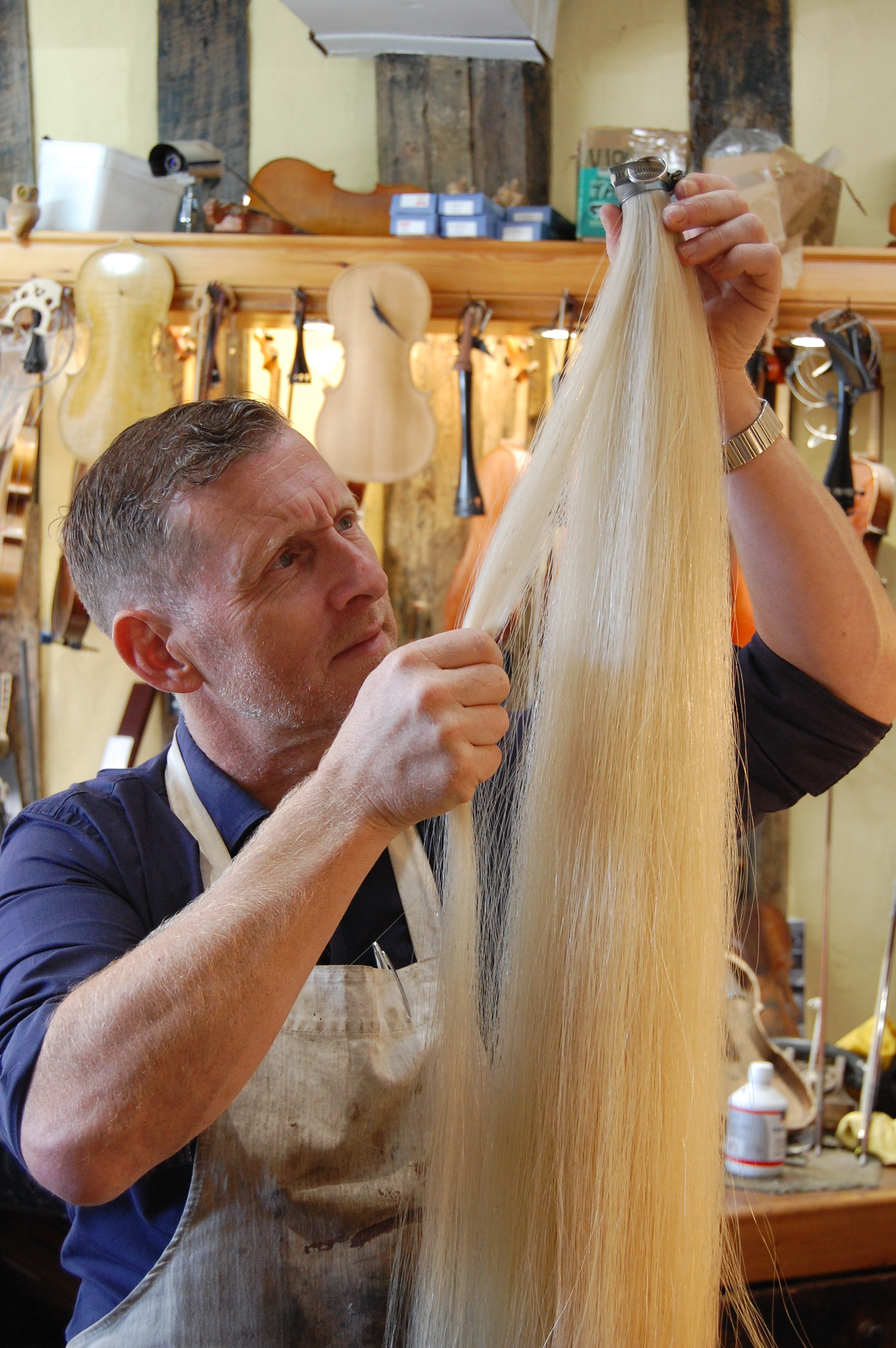 After dismantling the bow and discarding the old hair, the stick and metalwork needs to be fully cleaned.  After selecting the new hair, it must be very finely combed, ensuring that the individual hairs are not crossing one another which would cause the stick to warp. A violin bow needs aproximately 150 hairs, the hank pictured above lasts us around 2 months!