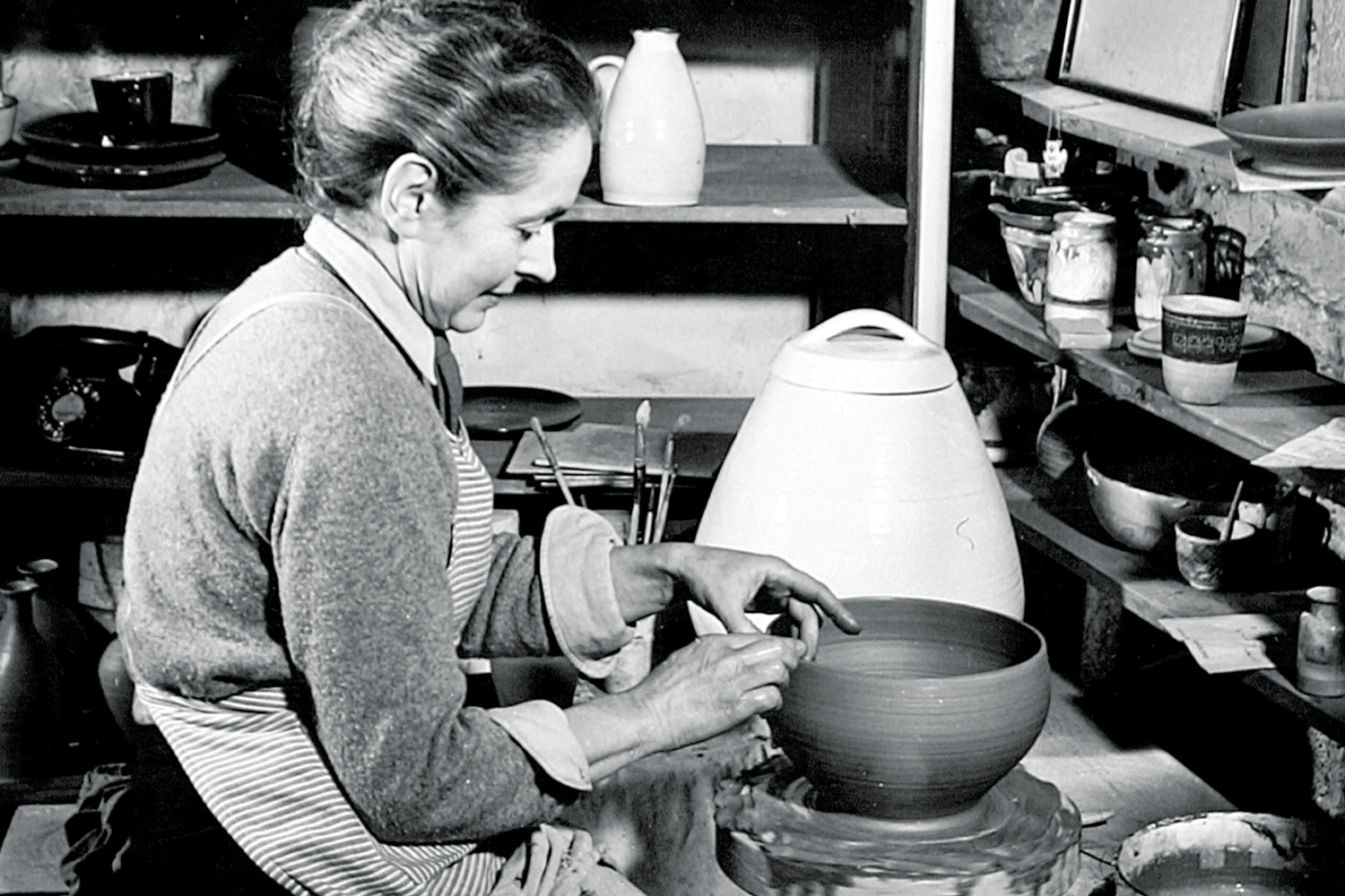 Feature:  Lucie Rie potting on the wheel in her studio at Albion Mews, 1951.  Image kindly provided by the Crafts Study Centre, University for the Creative Arts