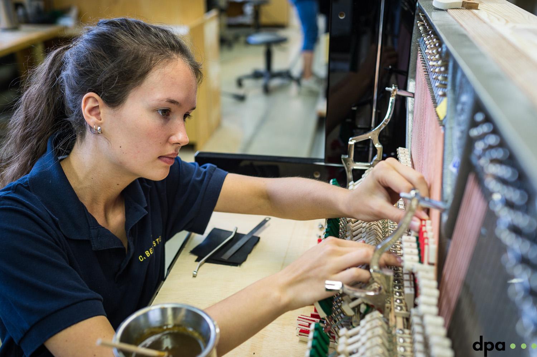 Auszubildende Paula Kiechle Leimt Daempfung auf in der technischen Pianoabteilung am 06.09.2017 in der C. Bechstein Pianofortefabrik AG in Seifhennersdorf (Sachsen). //Foto: Pawel Sosnowski