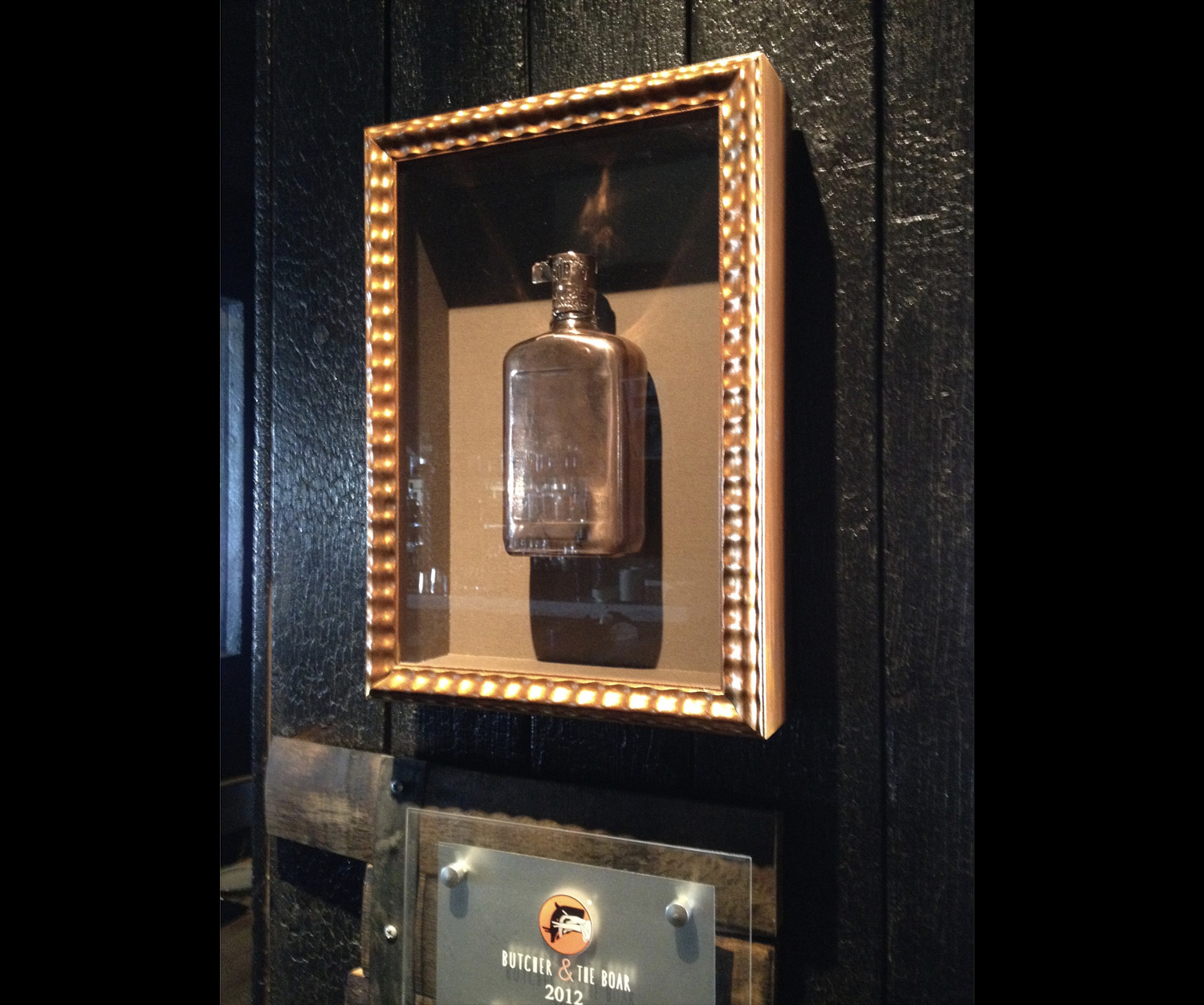 One of many whiskey bottles that we have framed for The Butcher and the Boar.