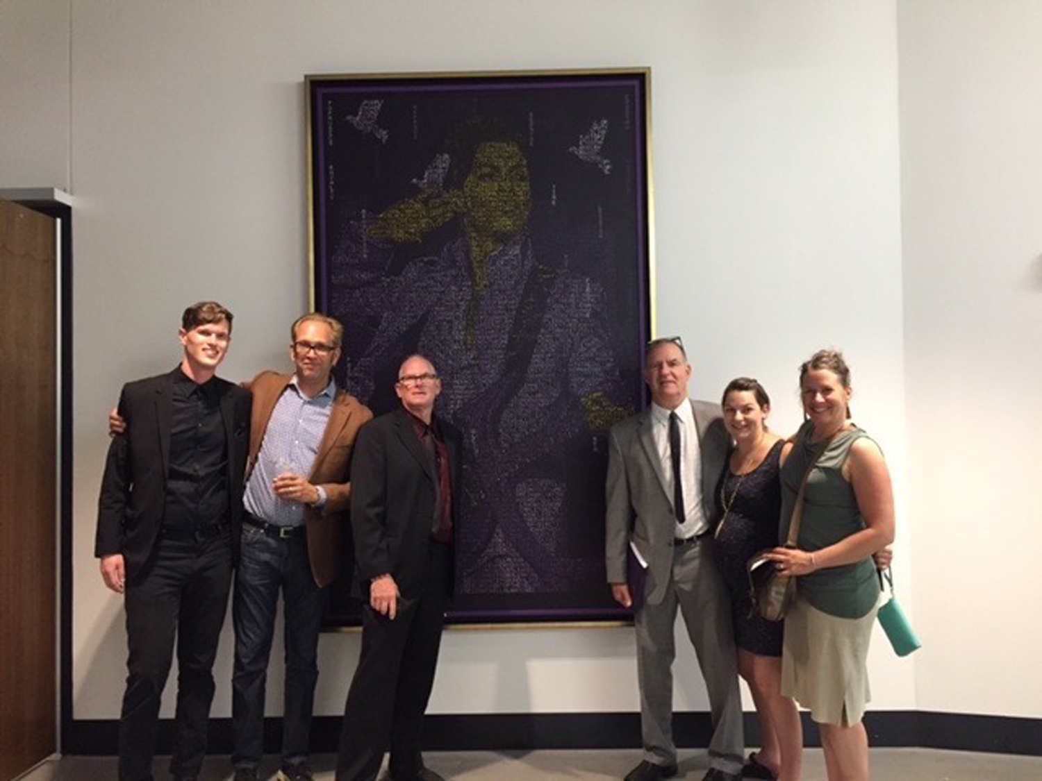 The Hang It crew at the art opening for the US Bank Stadium - standing in front of the Prince piece that we stretched and framed.