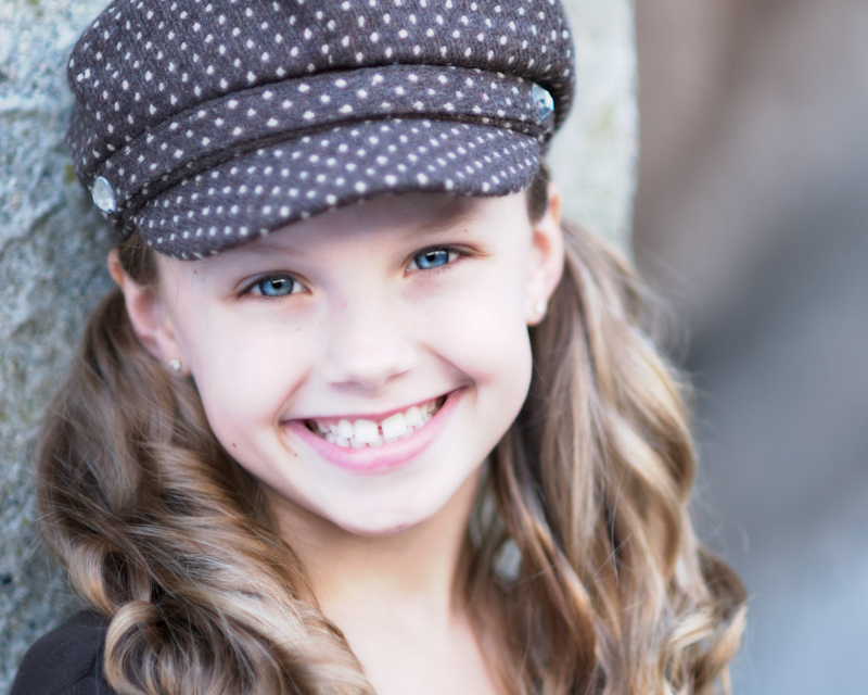Blue eyed girl in pokadot hat and pigtails