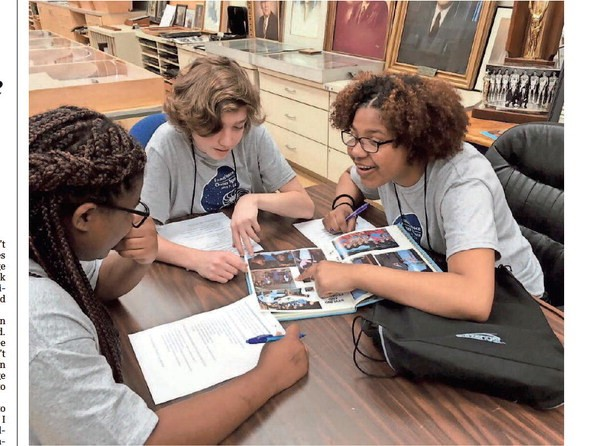 Current Austin-East students look at an Austin-East yearbook from 1989. Breanna Morris, Quincy Fields and Ahya Moreno are surprised to see that the school itself hasn't changed that much, though the faces certainly have.  (source) CAROL Z. SHANE/SHOPPER NEWS