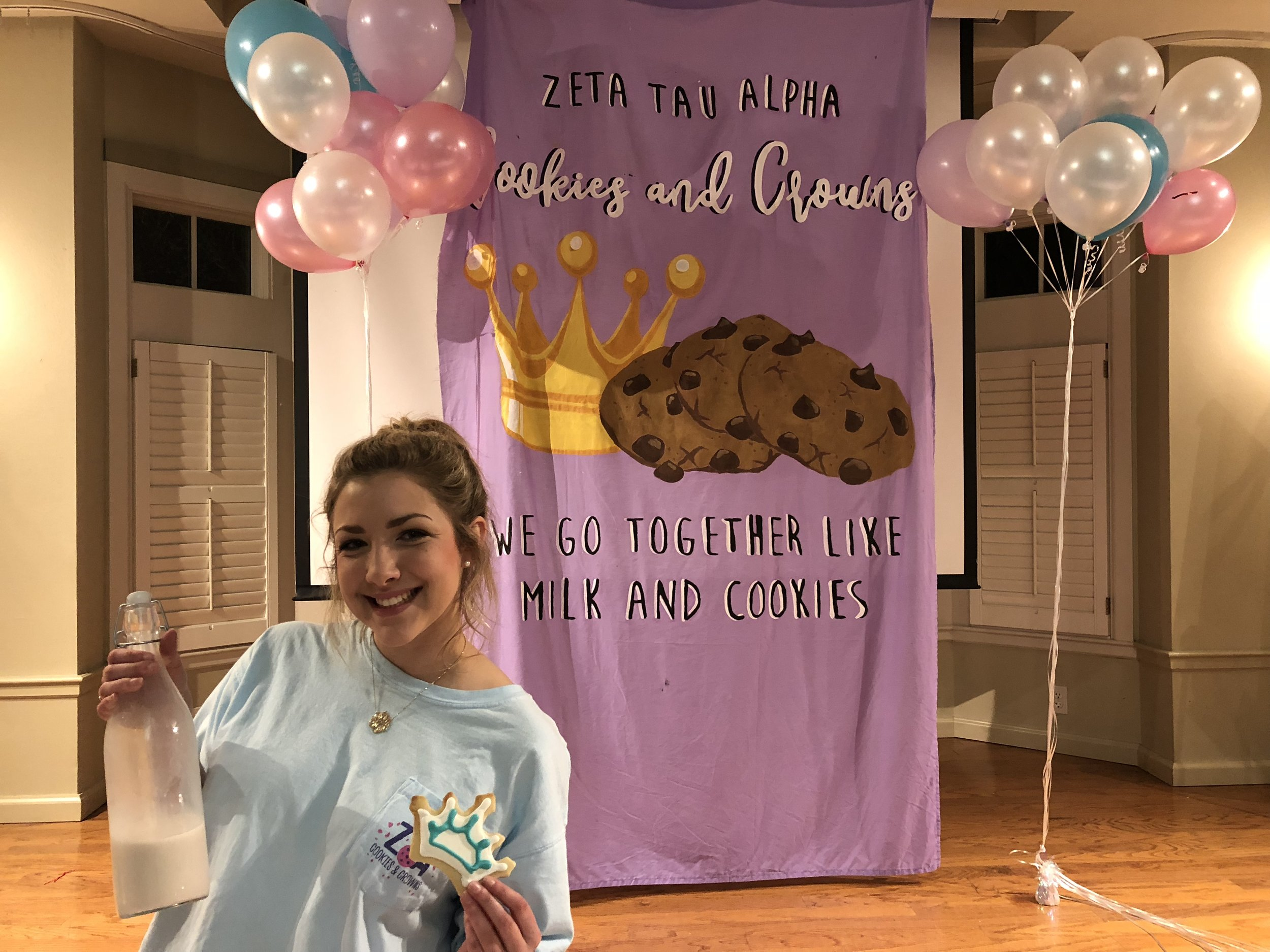 "Sarah Elliot poses in front of the ""Cookies and Crowns"" banner. She was so excited to share cookies and memories with the LSU community."