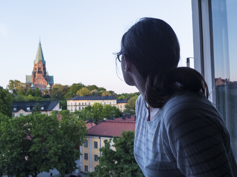 My wife enjoying the view of Sofia Kyrka in Nytorget through our apartment window during a long summer evening in Stockholm.