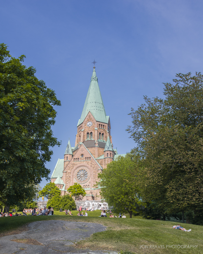 Stockholm residents enjoying a summer afternoon on the grounds of Sofia Kyrka in Nytorget.