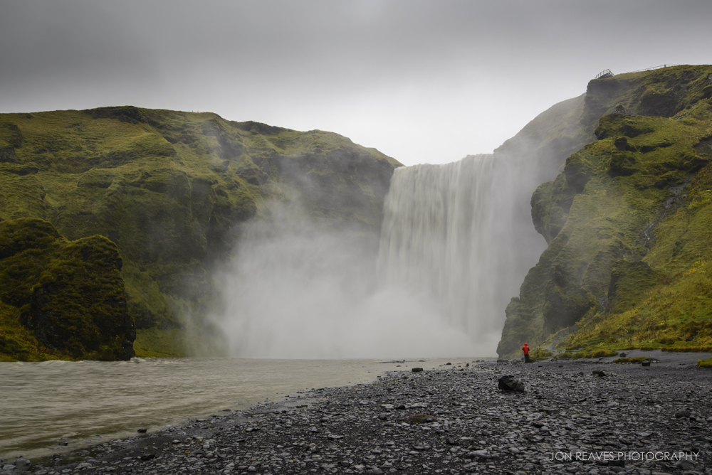 Skogafoss Waterfall, Iceland. Though this image was made at mid-day, the heavy overcast clouds allowed me to use slower shutter speeds and have no issues with glare or reflections. I used the person in the red coat to show scale. (Nikon D600, Nikkor 18-35G,  Sirui     T-025x Carbon Fiber Tripod with C-10 Ball Head)