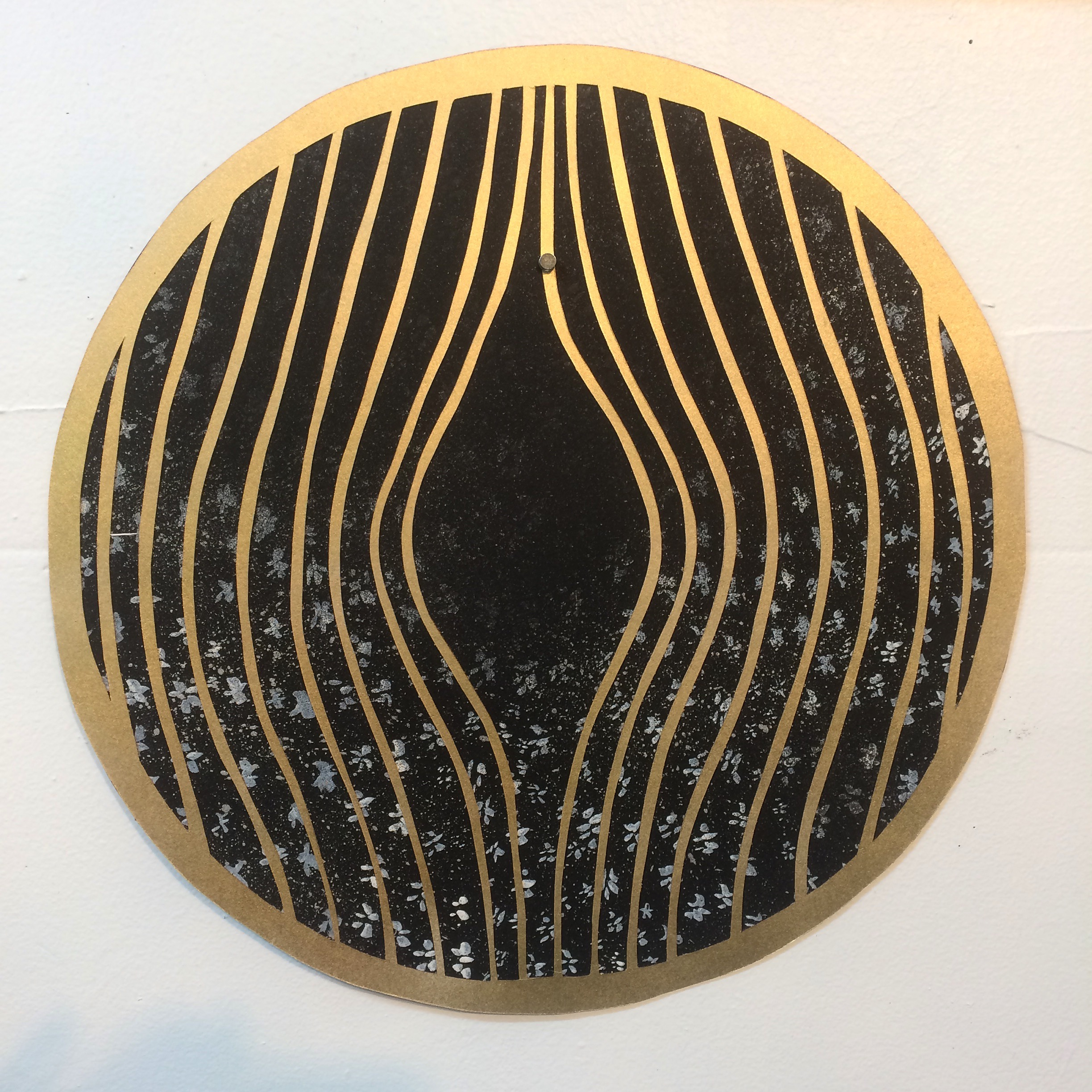 """10""""x10"""" Gold paper cutout on painted paper back-ground."""