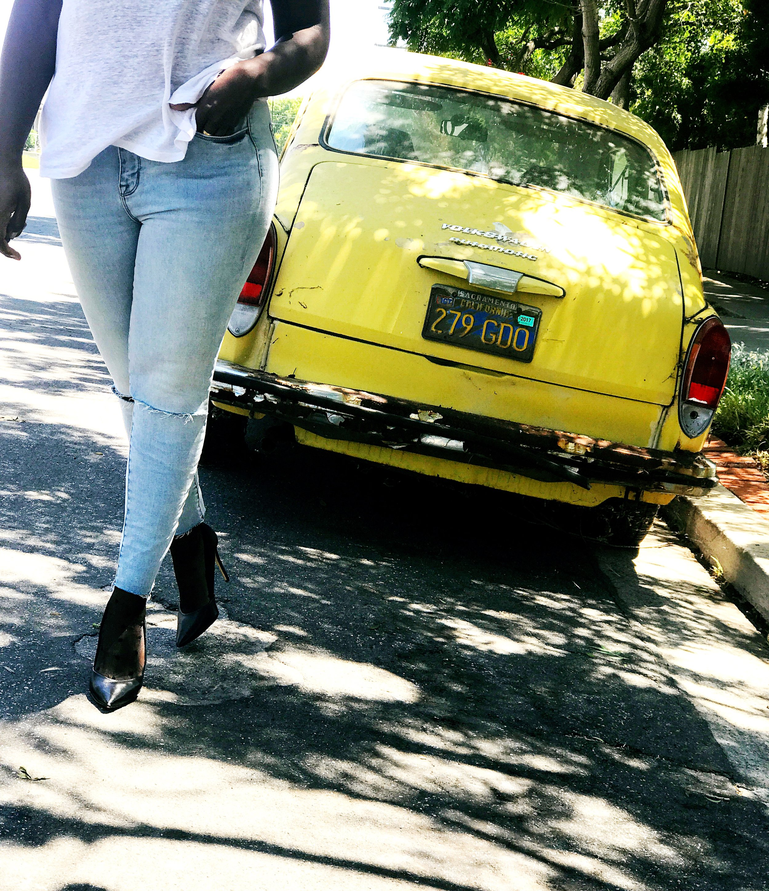 Black woman walking away from old yellow car wearing ripped jeans and t-shirt
