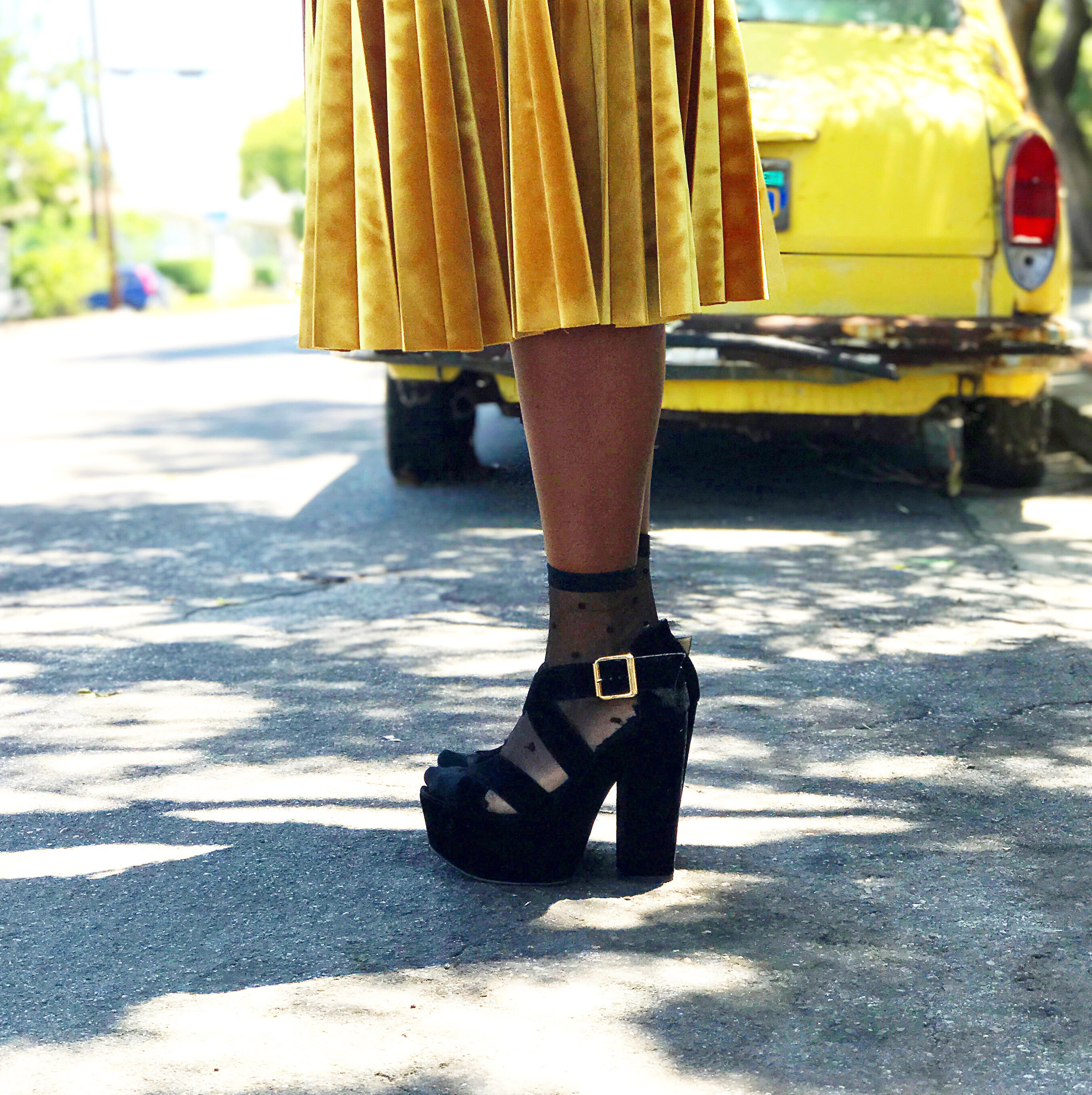 Woman wearing chunky heeled sandals, sheer socks, and gold pleated velvet skirt from Top Shop
