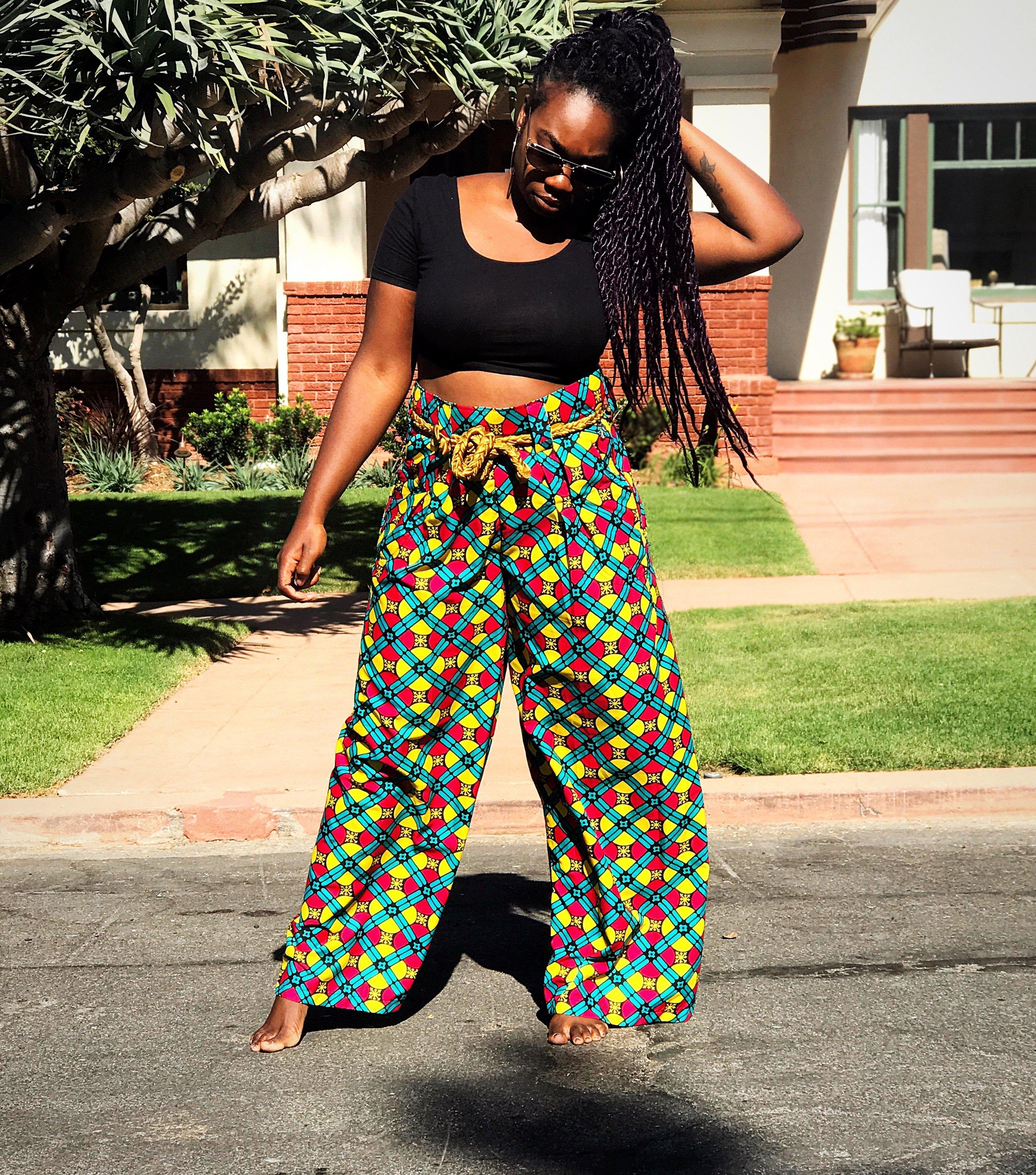 Femi wearing ankara print wide leg pants and black crop top standing in the street #BlackGirlMagic