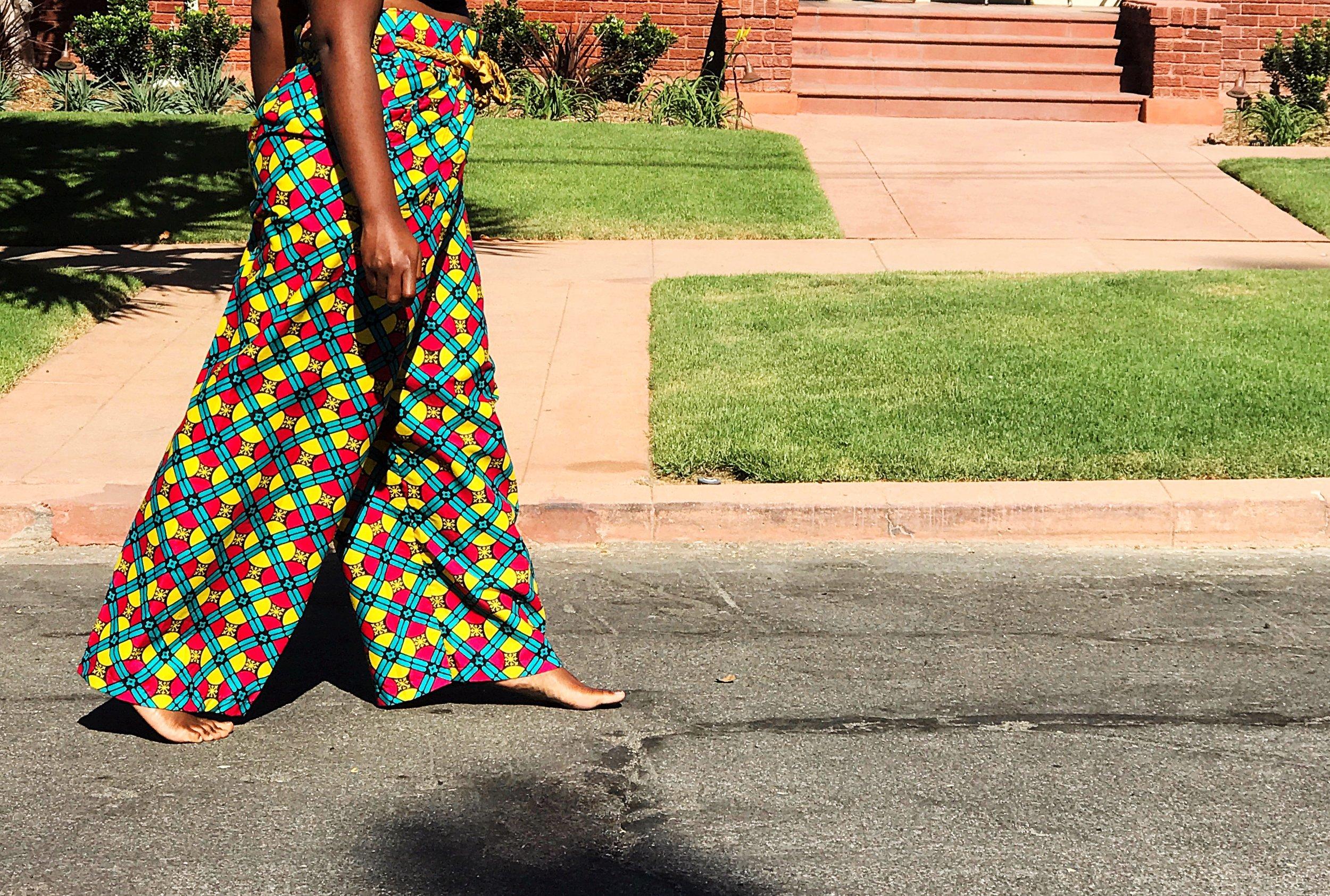 Black woman walking barefoot in street wearing wide leg ankara pants